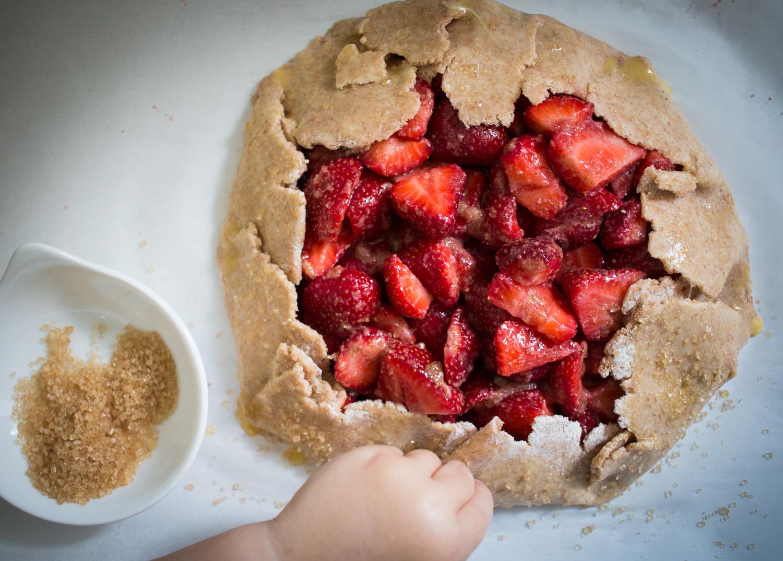 sprinkling sugar on strawberry galette