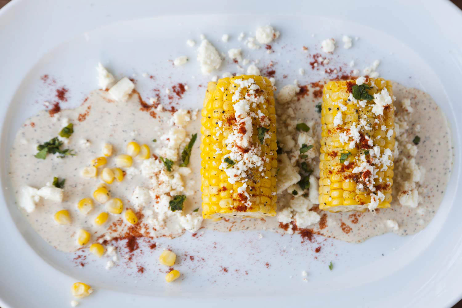 Corn on cob garnished with herbs and spices