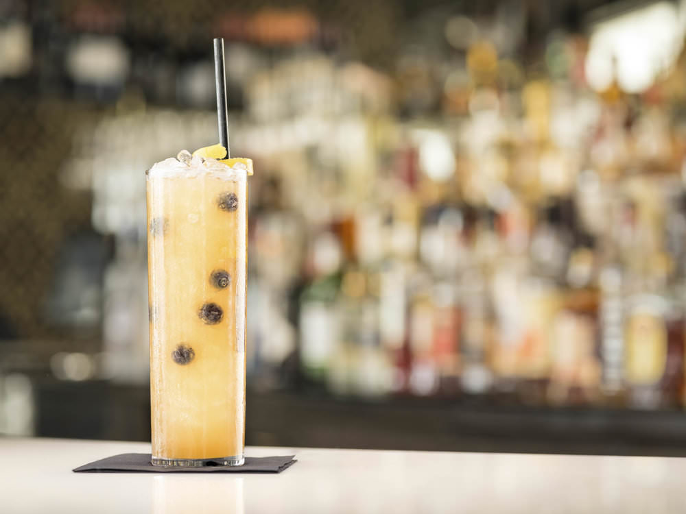 A styled photograph of a cocktail on a bar