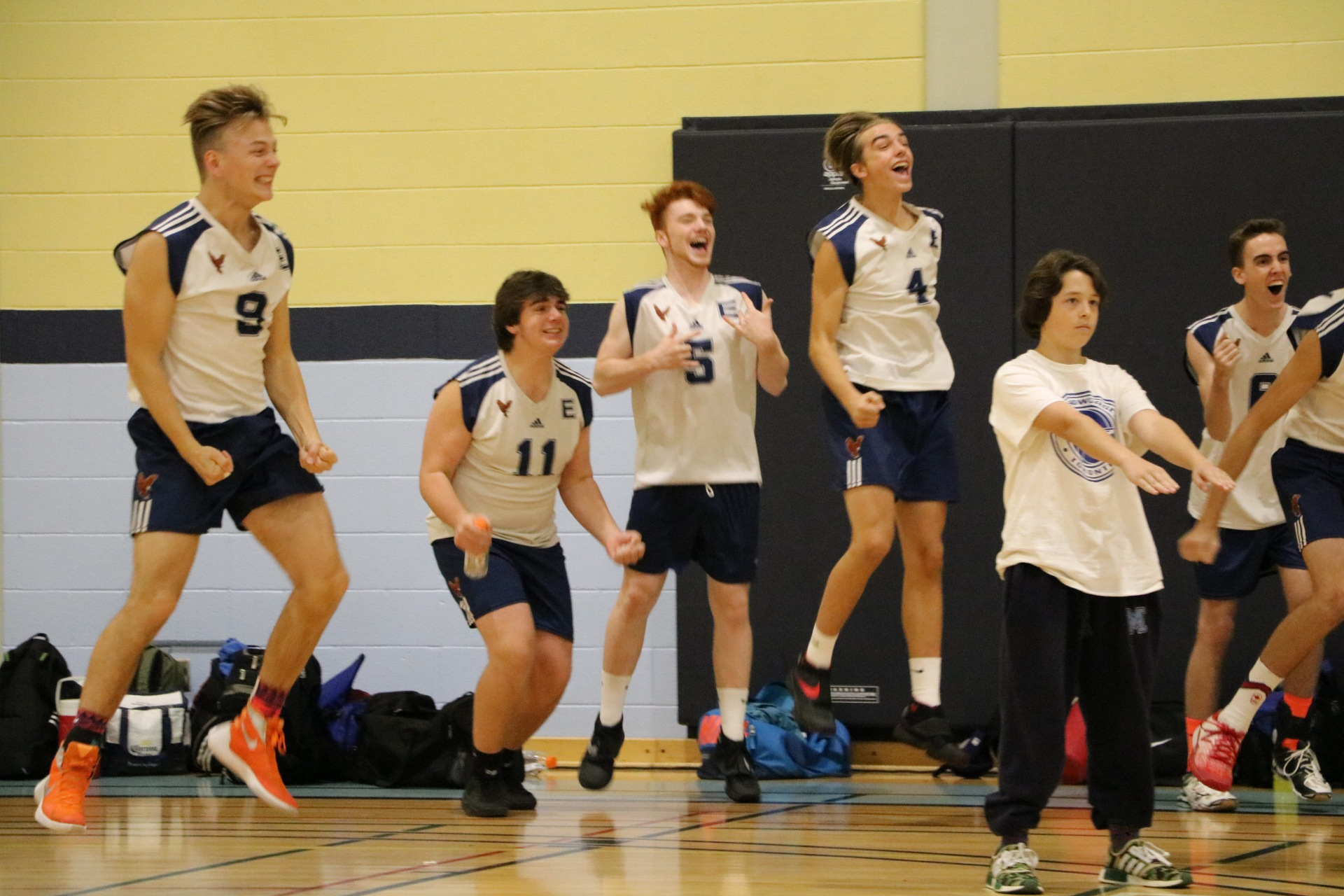 Senior boys volleyball team celebrating a point in the playoffs.
