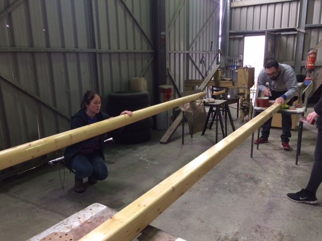 Volunteers hand sanding the mast of an historic Galway Hooker being restored in Galway.