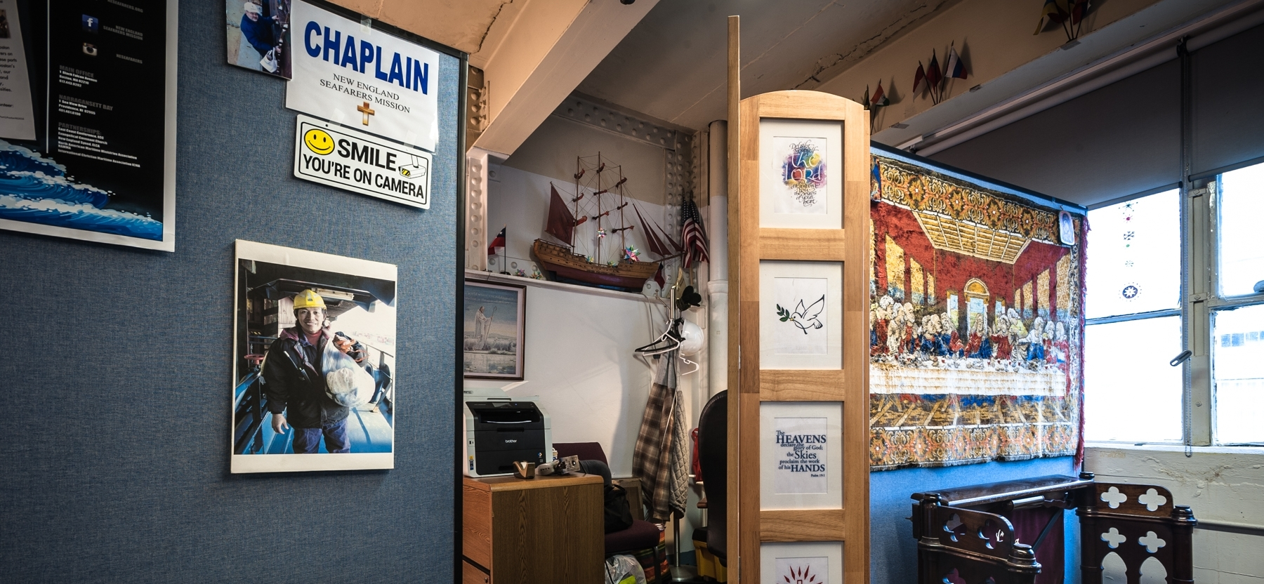 A kneeler, privacy screen and tapestry form the simple sacred space at New England Seafarers Mission