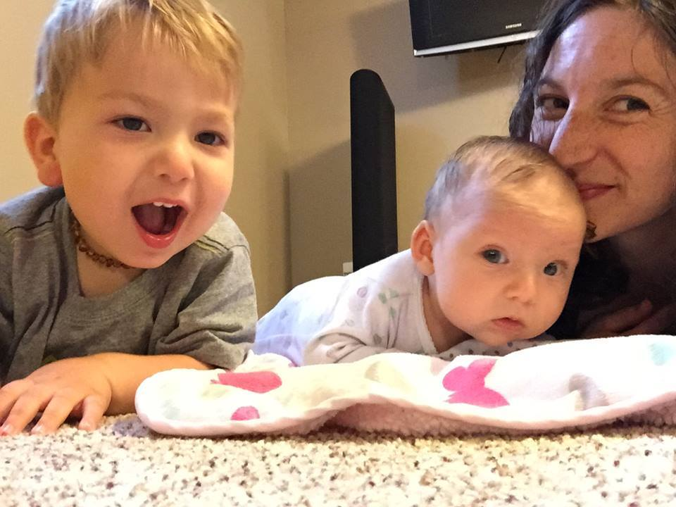 Baby in tummy time with sibling and parent