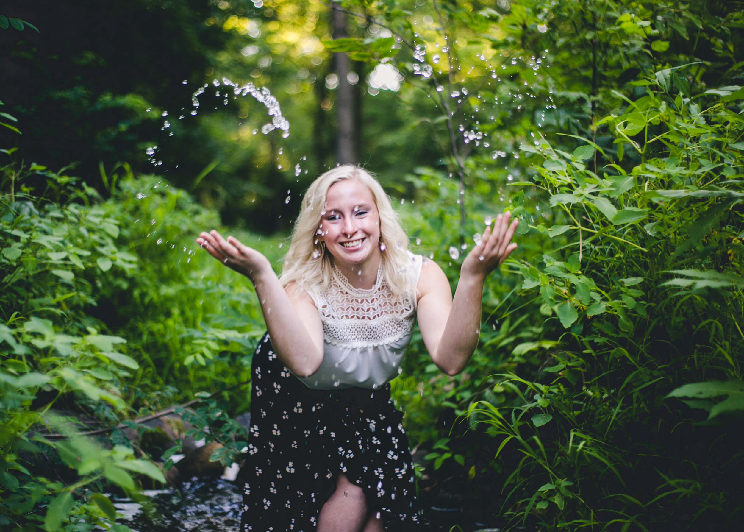 Girl smiles and throws water from stream