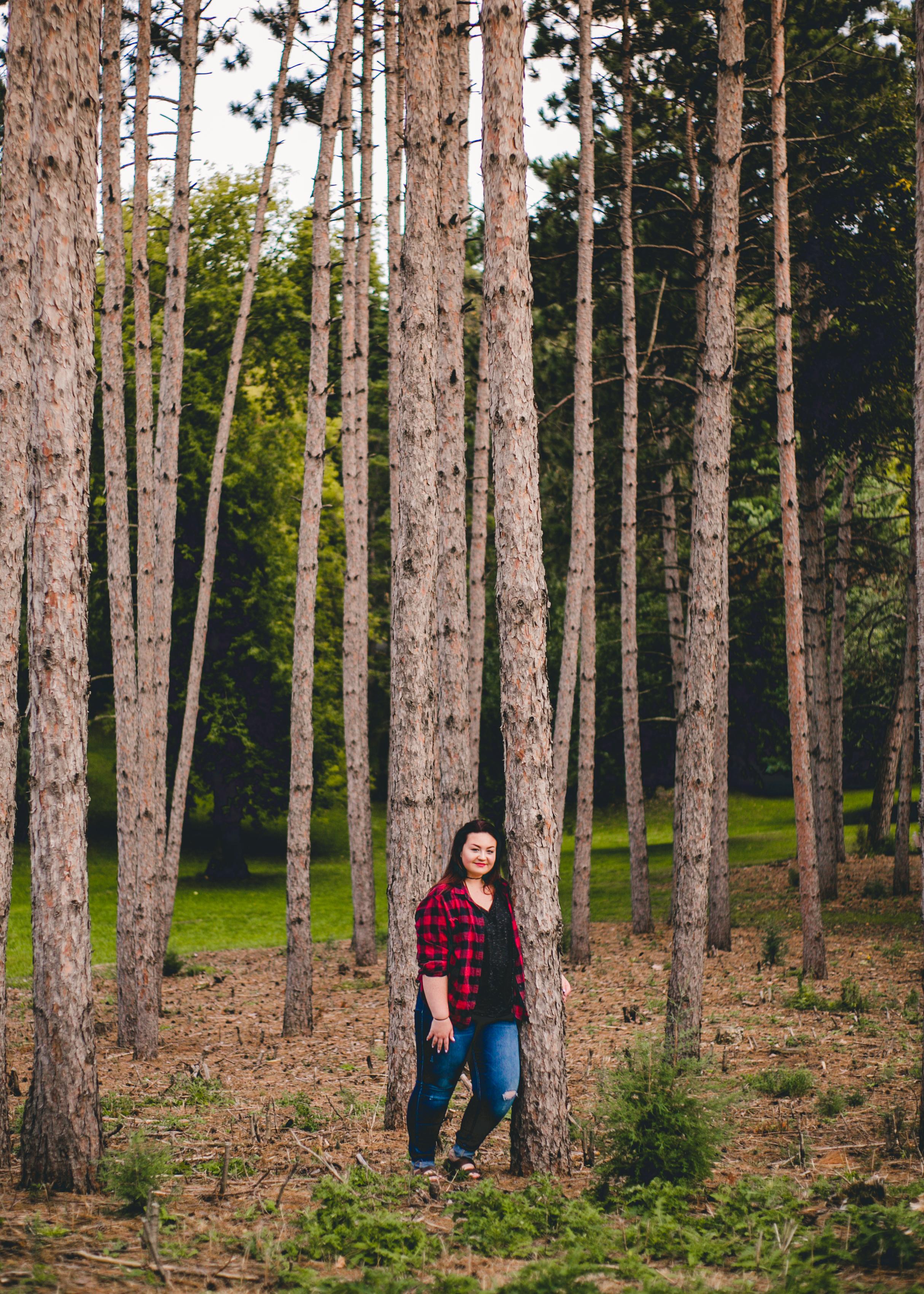 Senior in flannel posing against trees