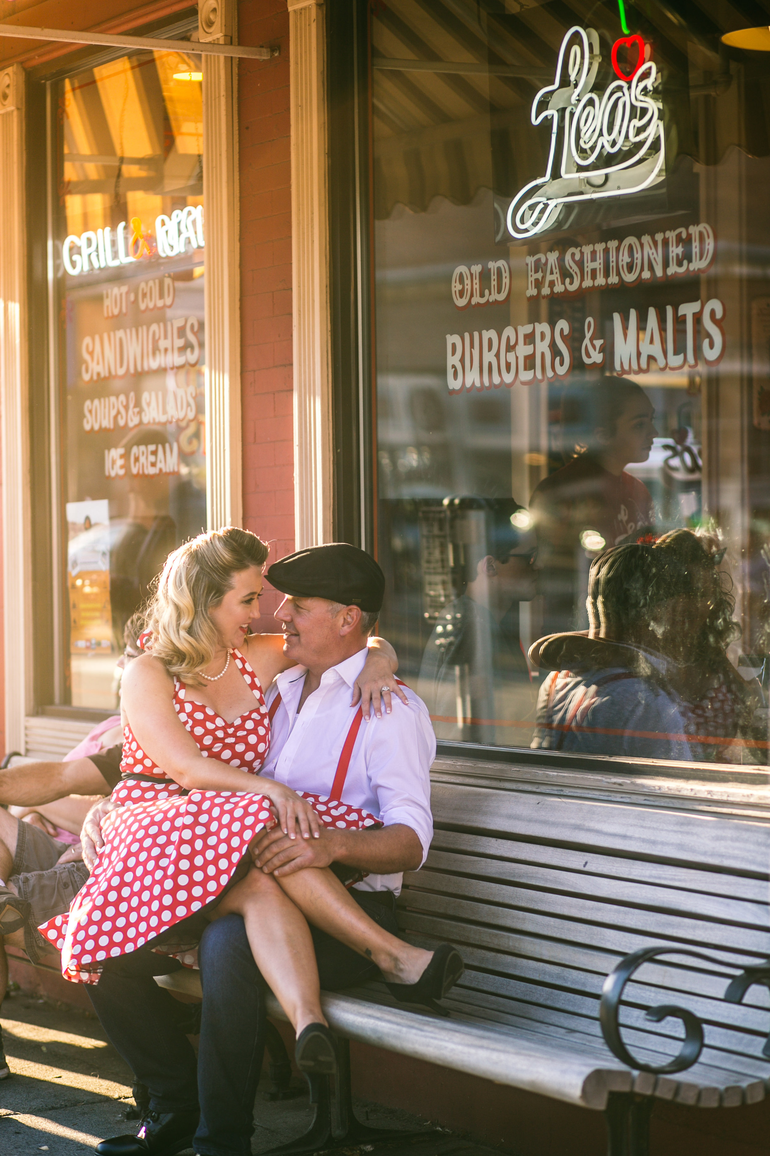 A 1940's vintage couple kissing in front of Leo's Ice Cream in Stillwater MN during their engagement session