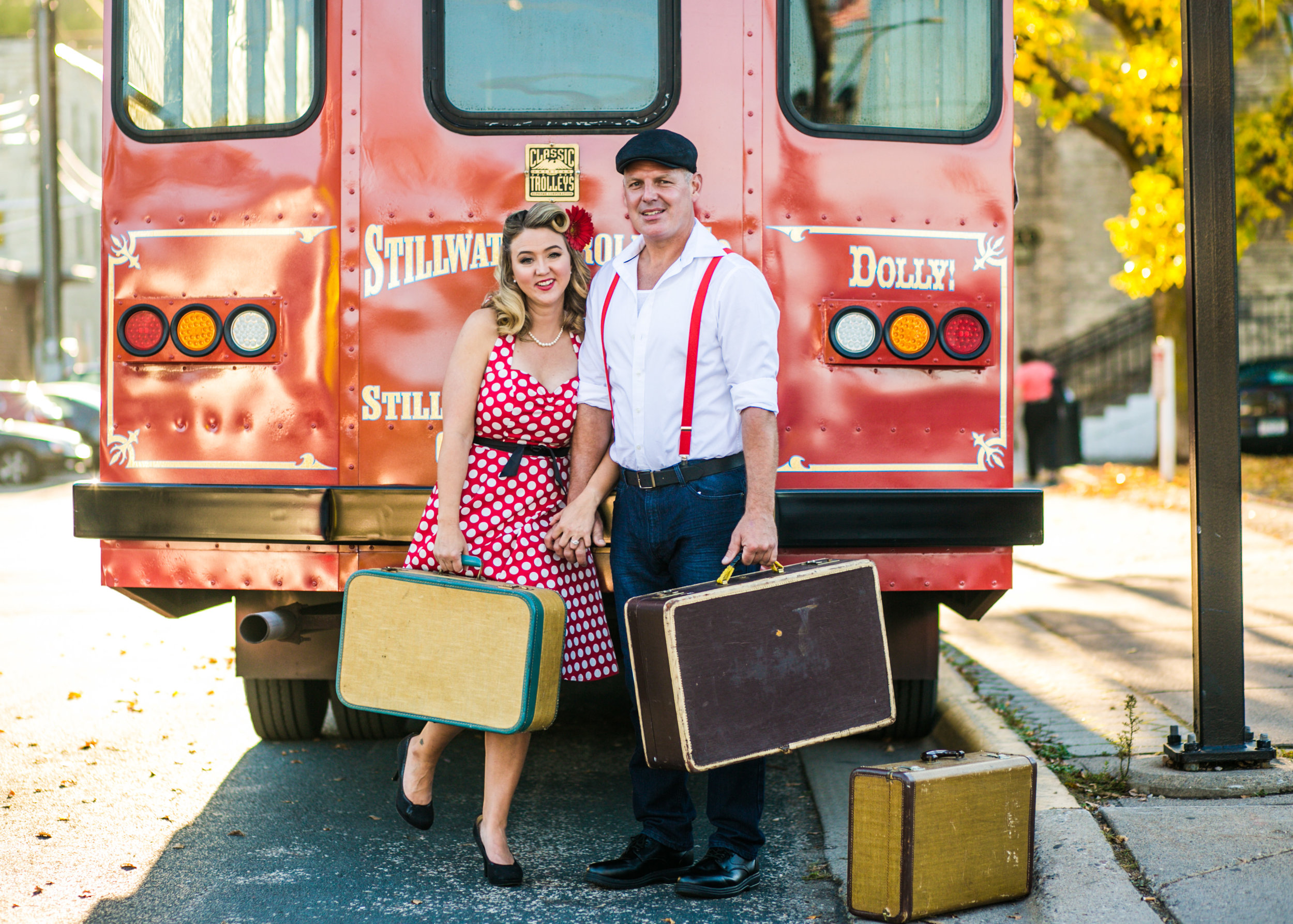 A couple poses with suitcases in front of the Stillwater Trolley during their engagement session with Andrea Wagner Photography