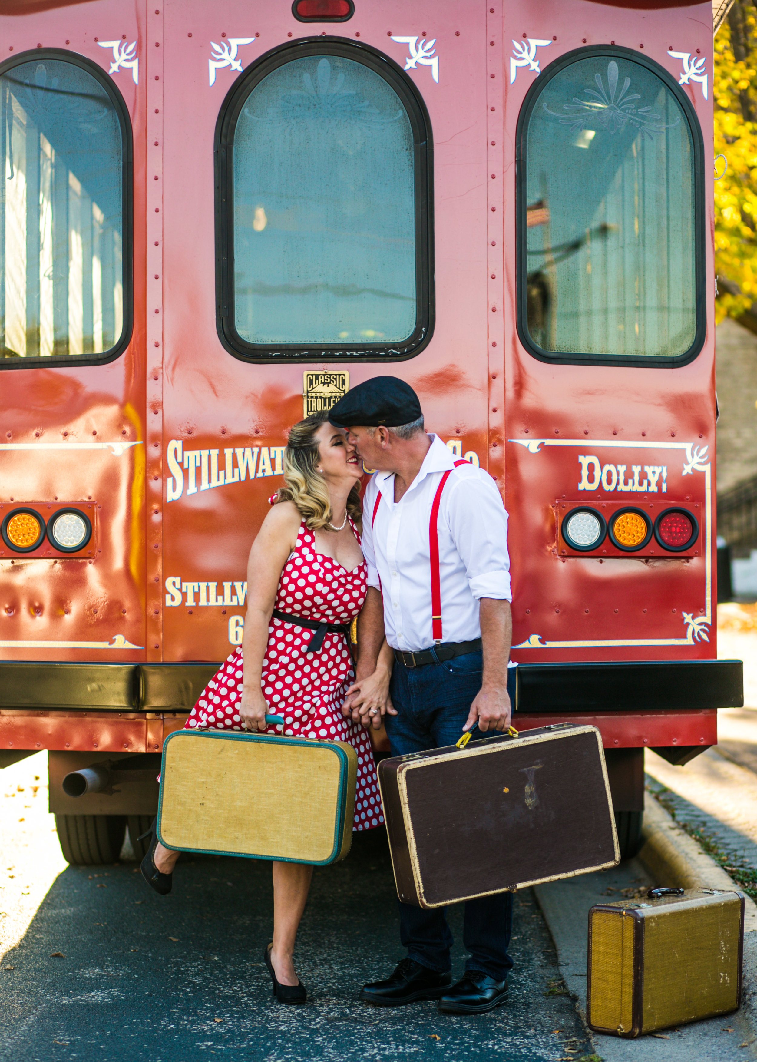 A couple kisses holding suitcases in front of the Stillwater Trolley during their engagement session