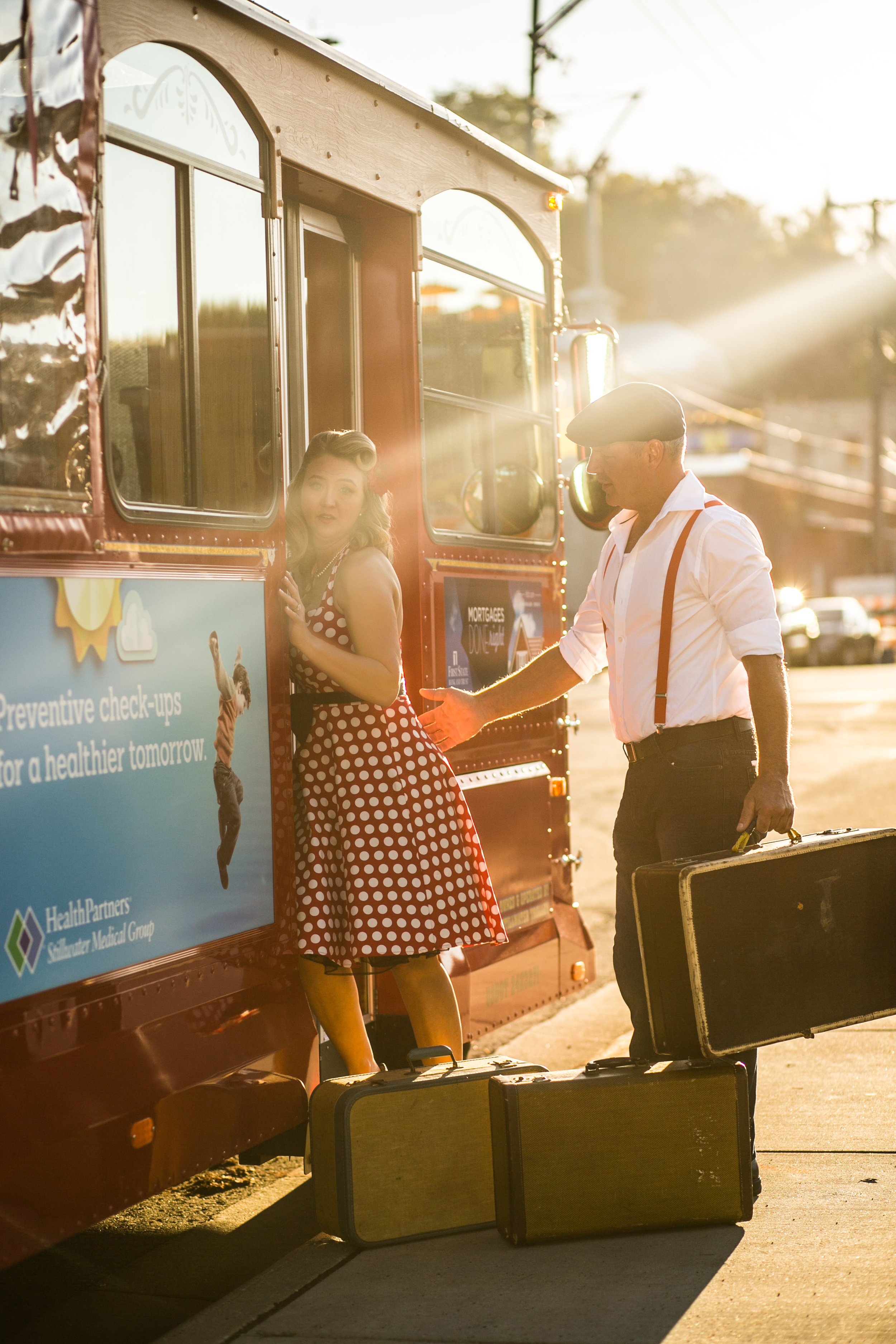 Vintage 1940's looking couple poses in front of Stillwater Trolley in the sunset causing flares