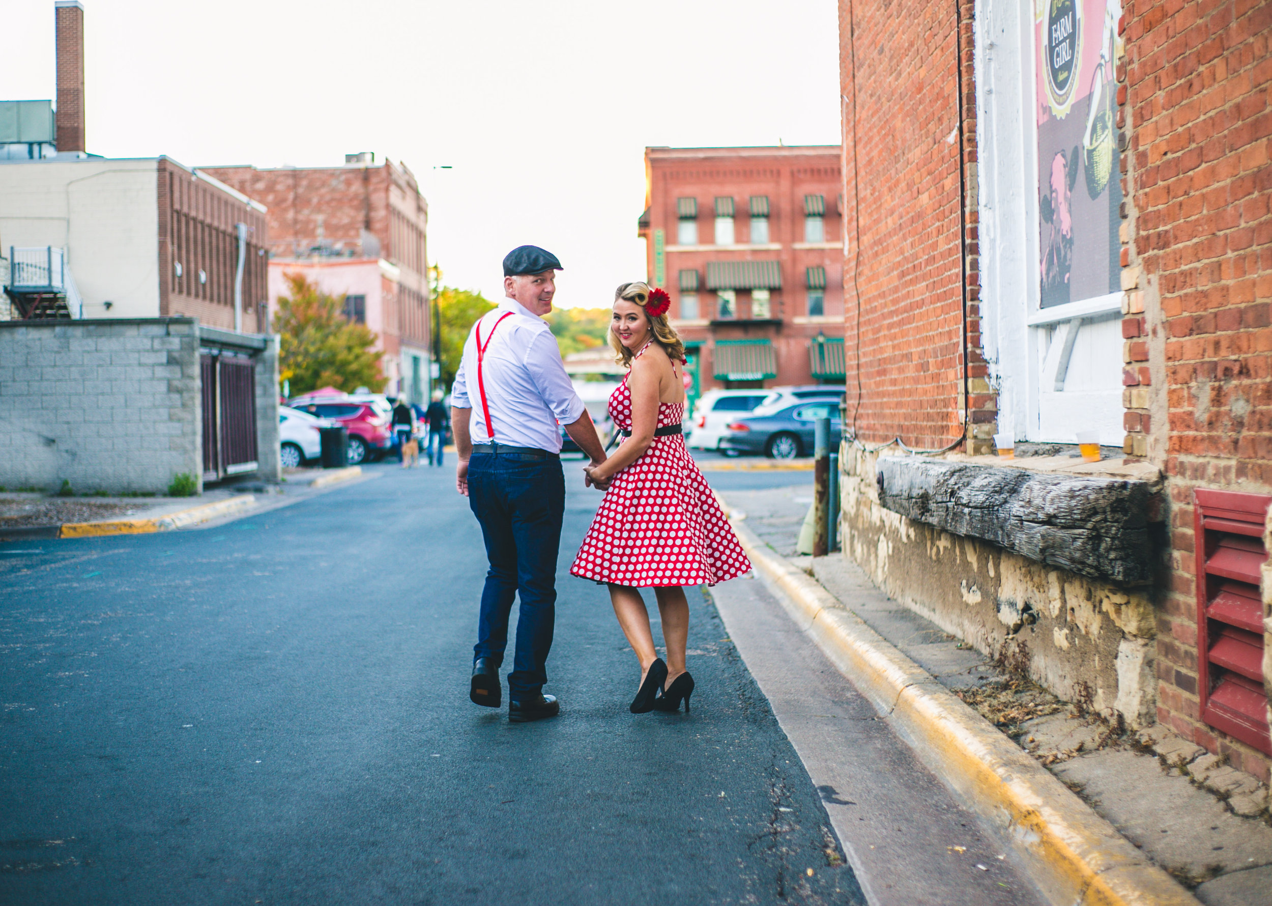 Vintage travel-inspired engaged couple walk down the alley of Stillwater MN