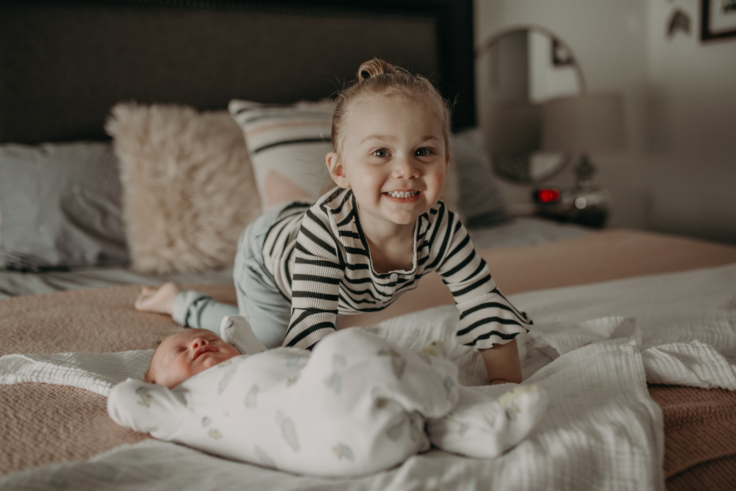 big sister smiling at little brother on bed