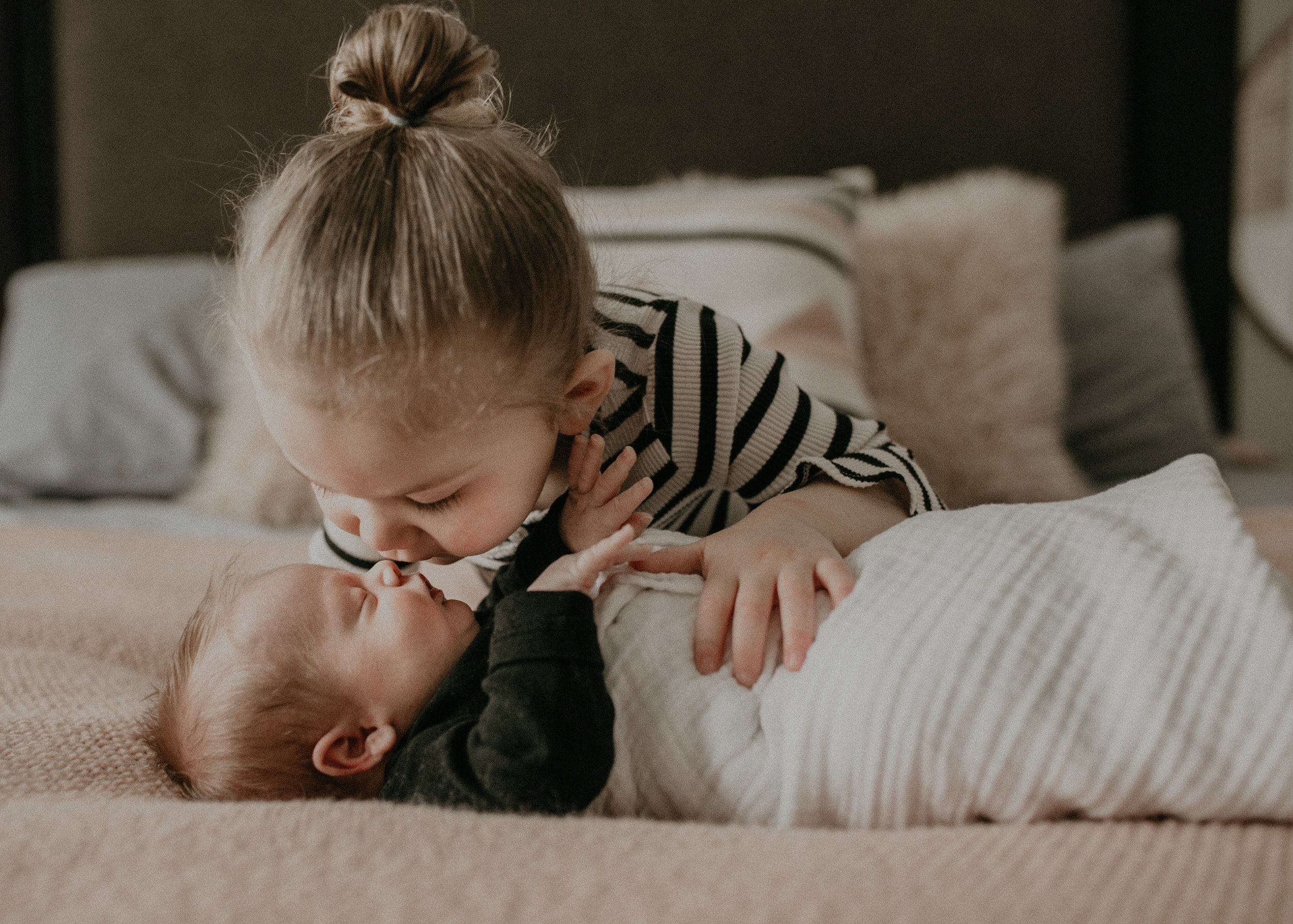 big sister kissing baby newborn brother on bed