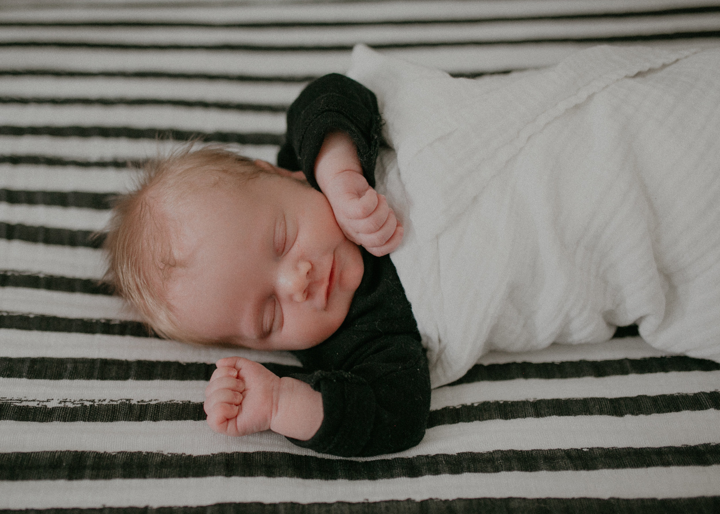 smiling newborn baby boy on black and white striped sheet