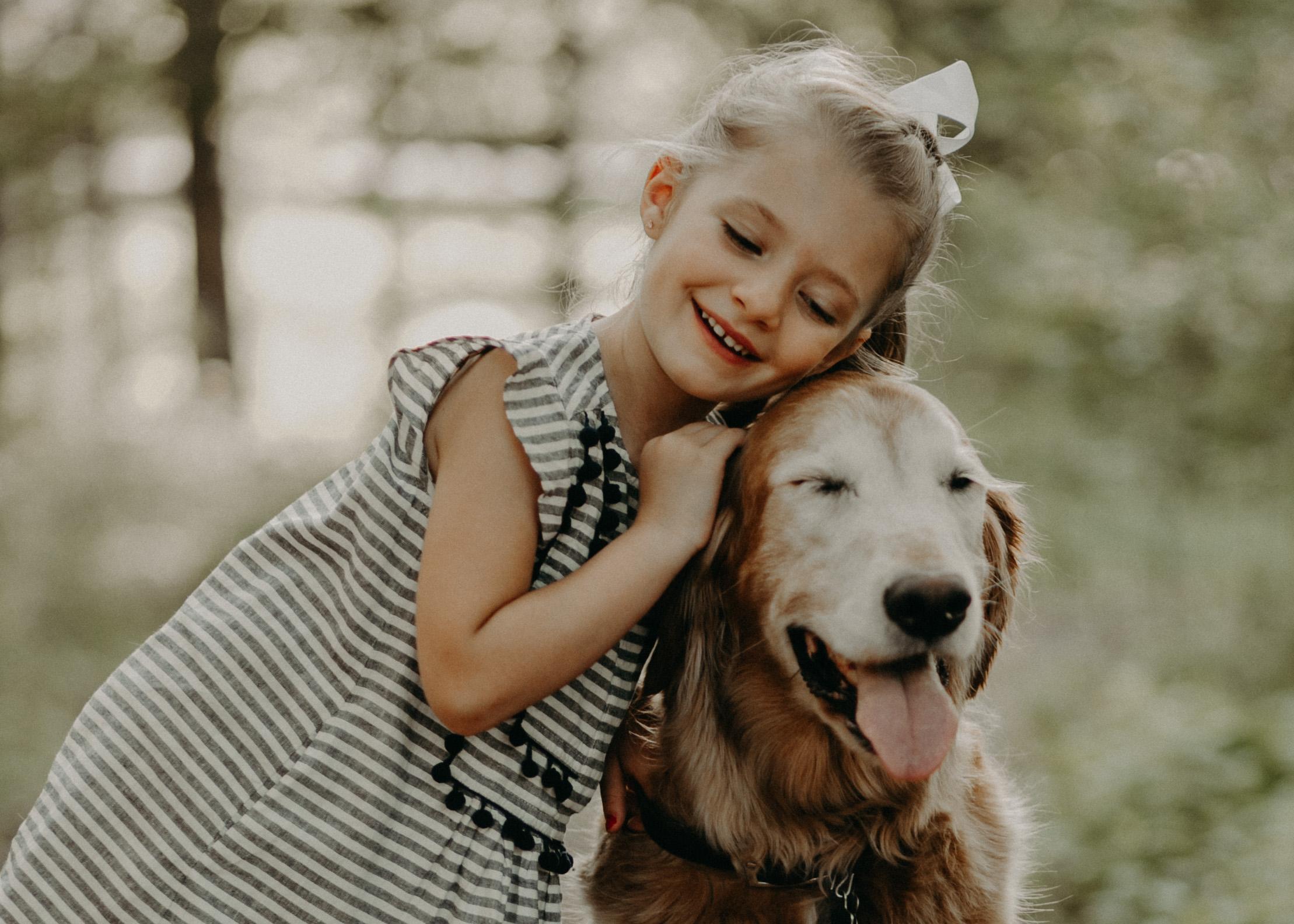 little girl hugging her golden retriever in River Falls WI