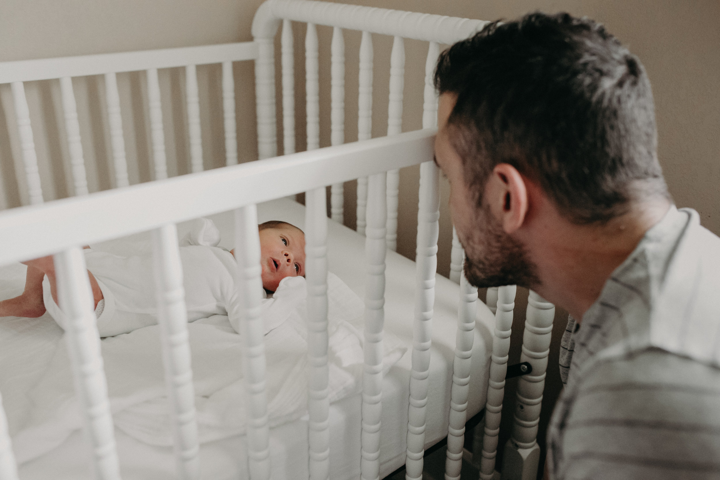 new dad looking at newborn baby in white crib