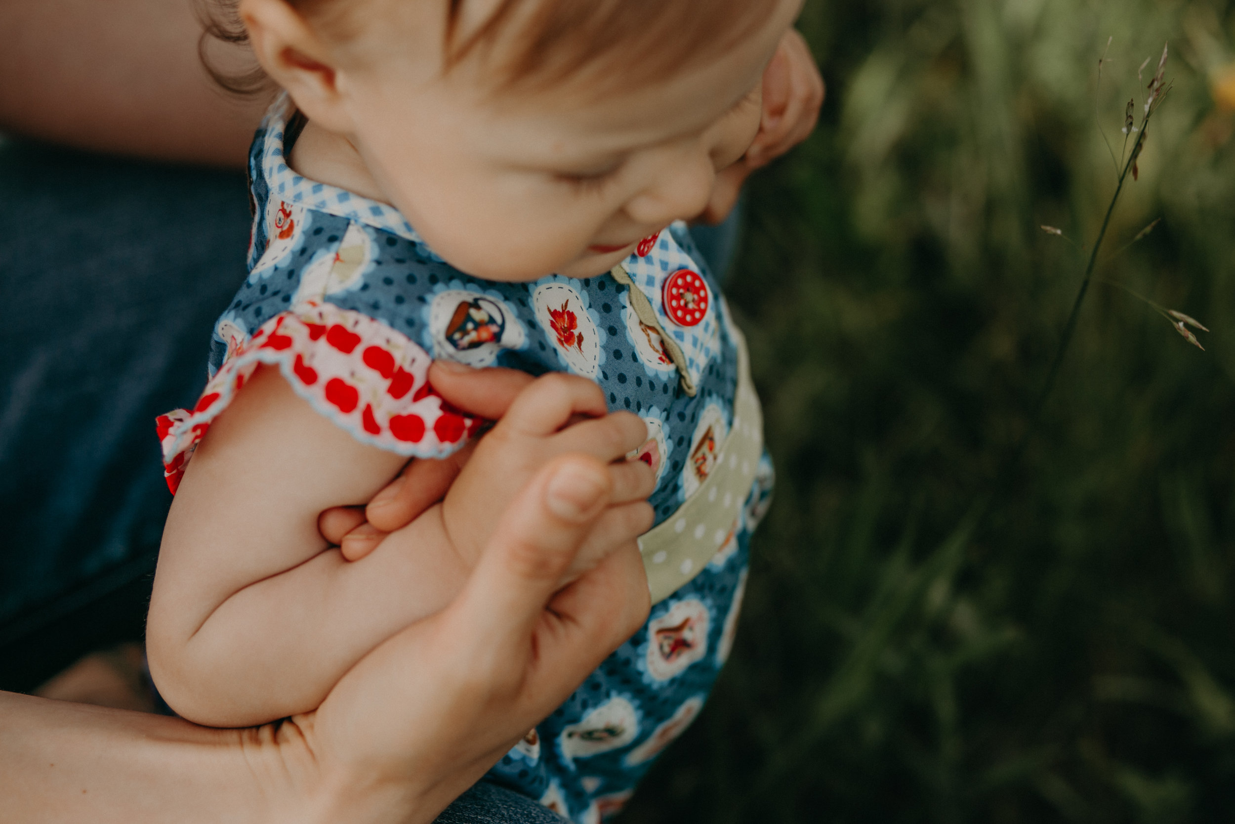 mommy holding baby girl's hands in a field in River Falls WI