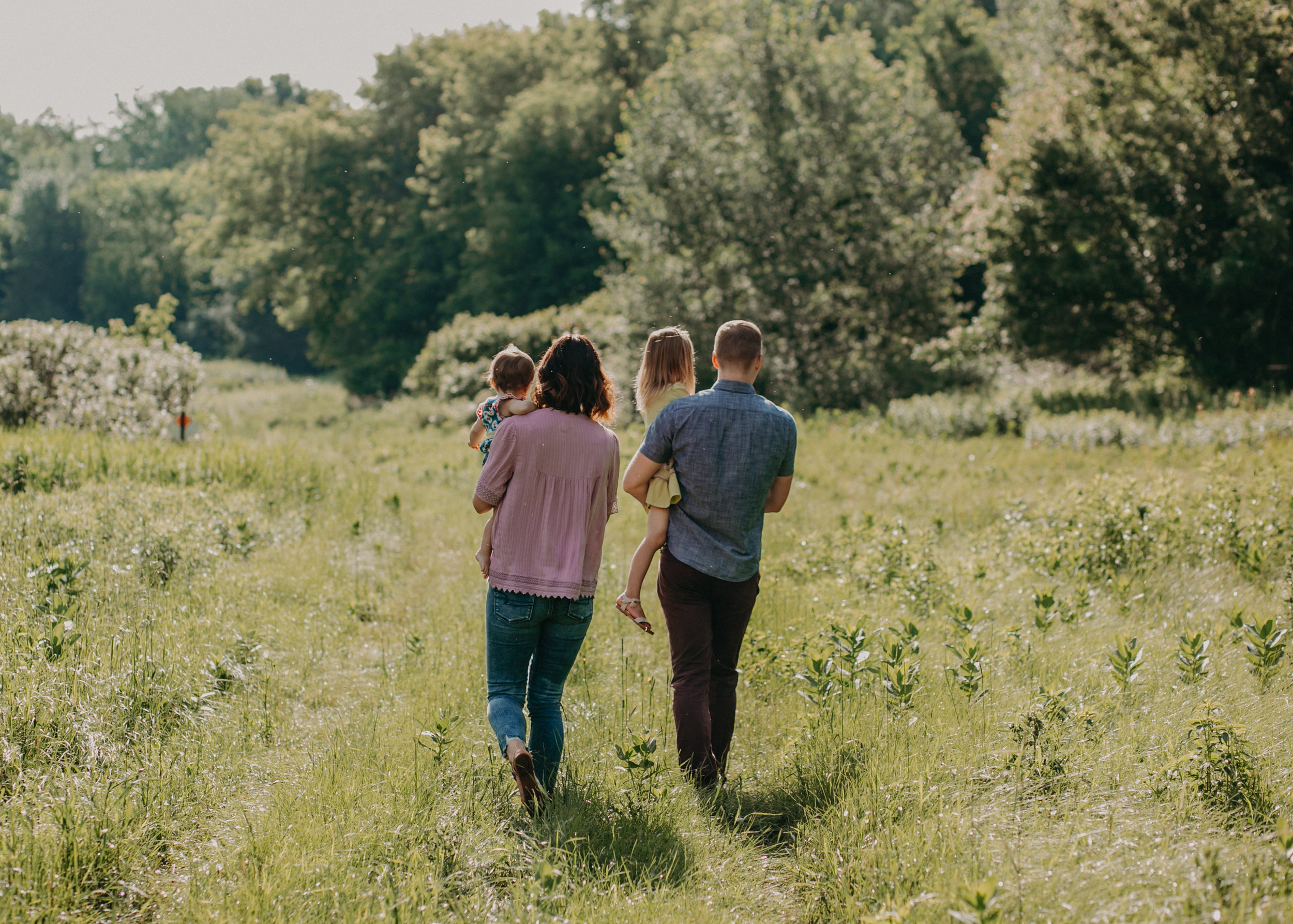 family walking from behind during family photo session in River Falls WI with Andrea Wagner Photography