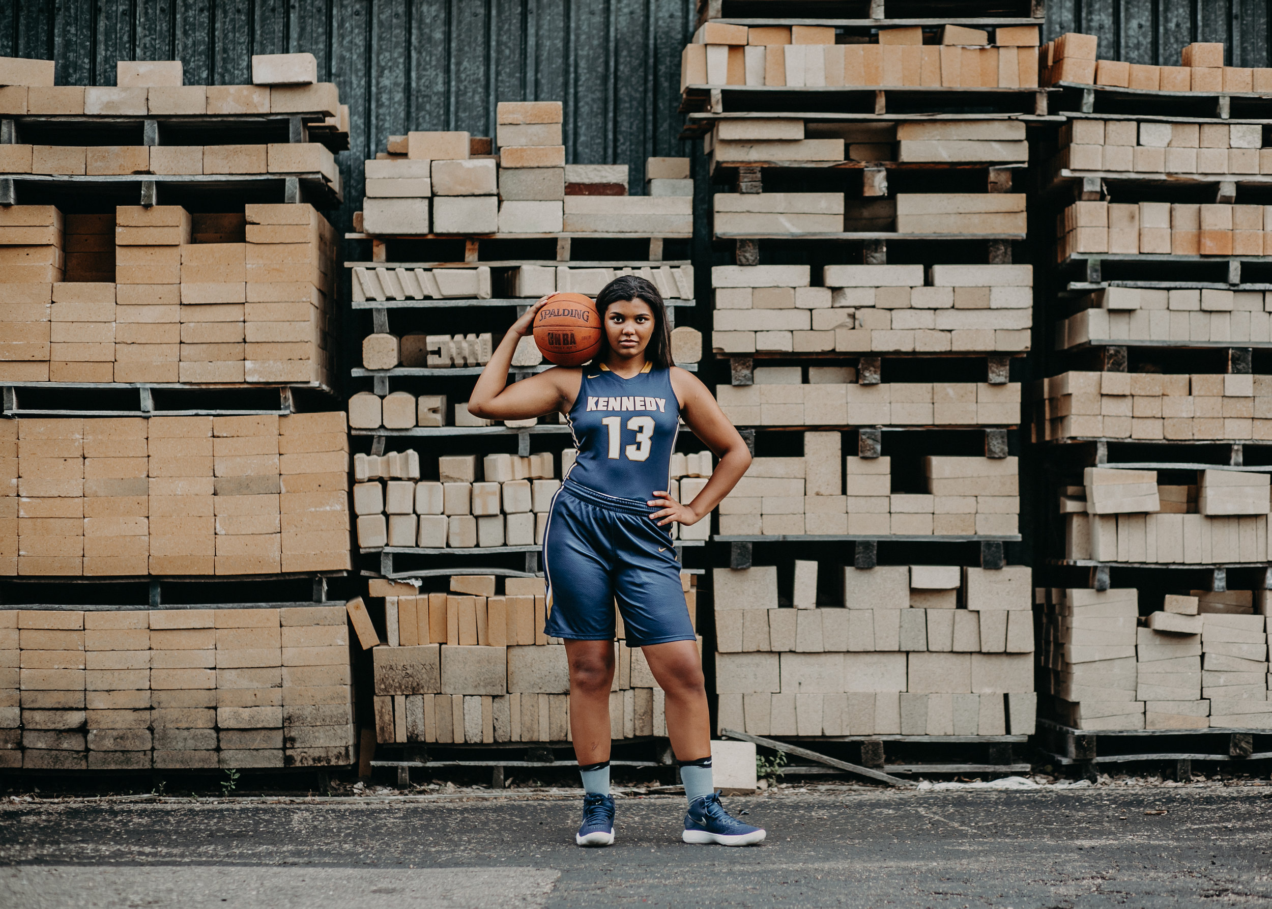 Basketball player in Hudson WI posing by pallets for her senior photo session with Andrea Wagner