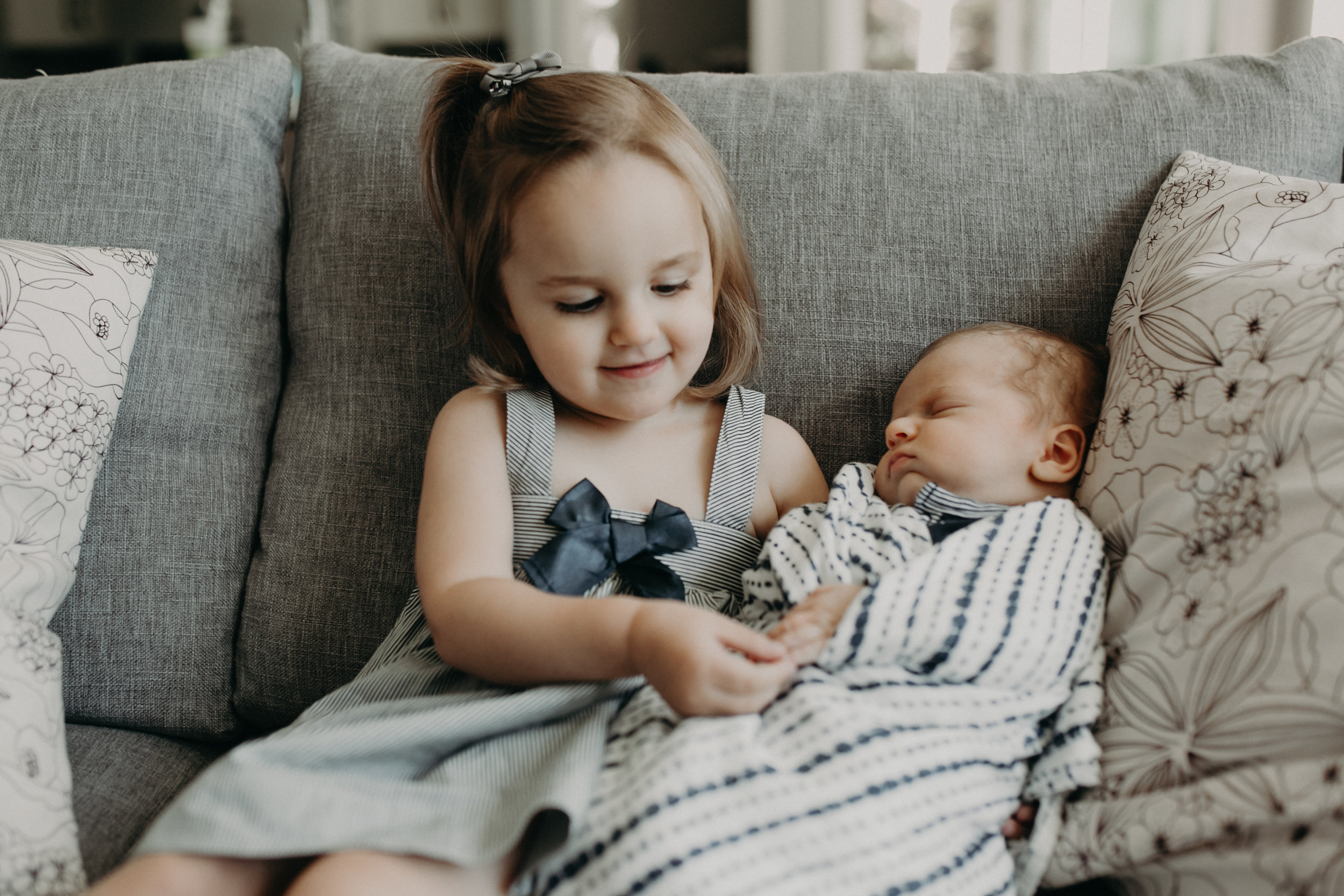 big sister playing with newborn brother's hands