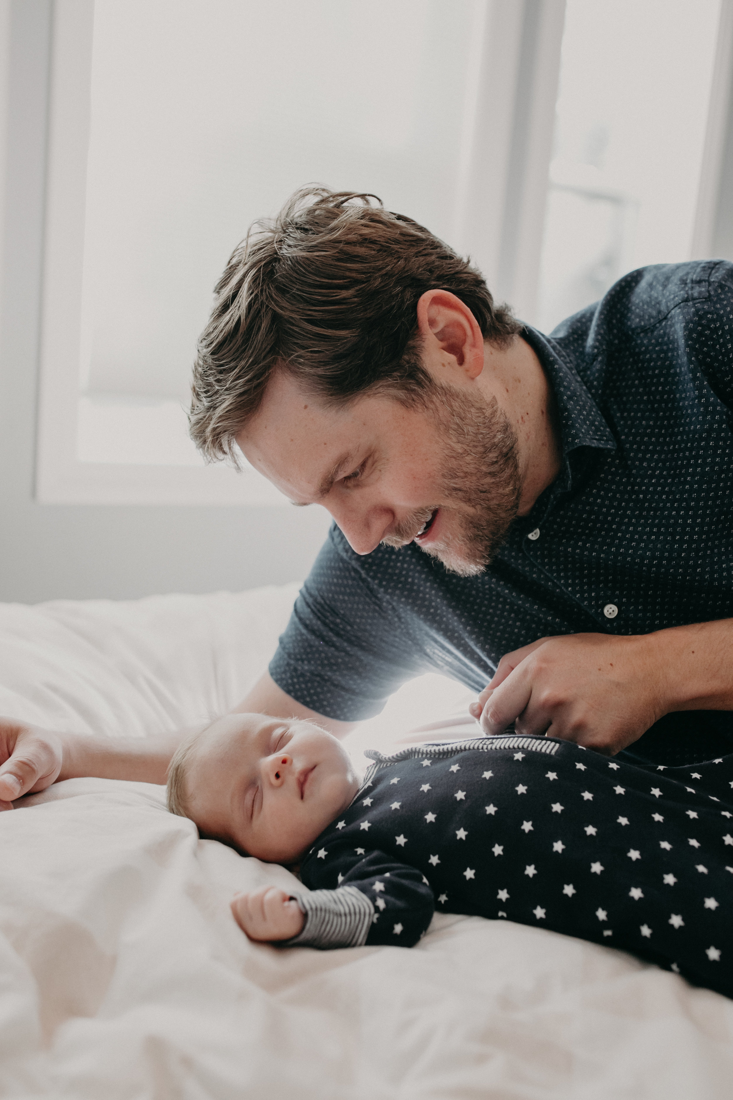 daddy and newborn baby boy laying on bed in their home in Wausau Wisconsin
