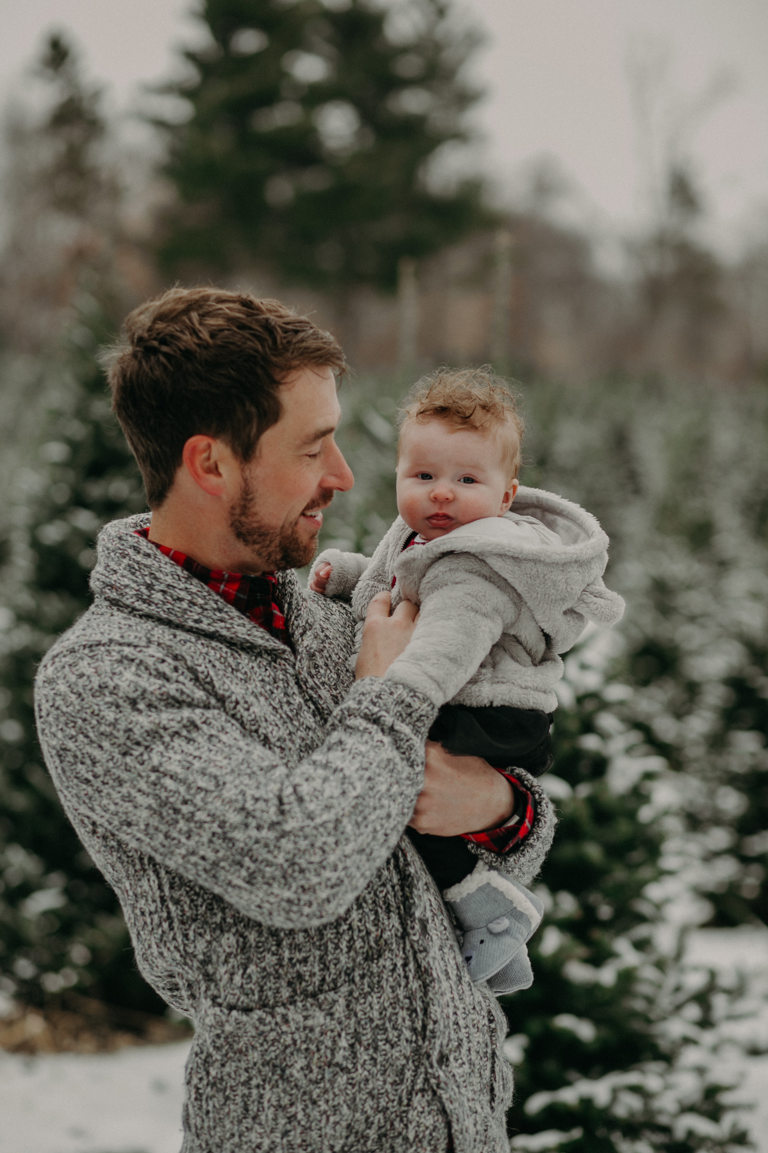 daddy and baby daughter at Christmas tree farm in Hudson WI