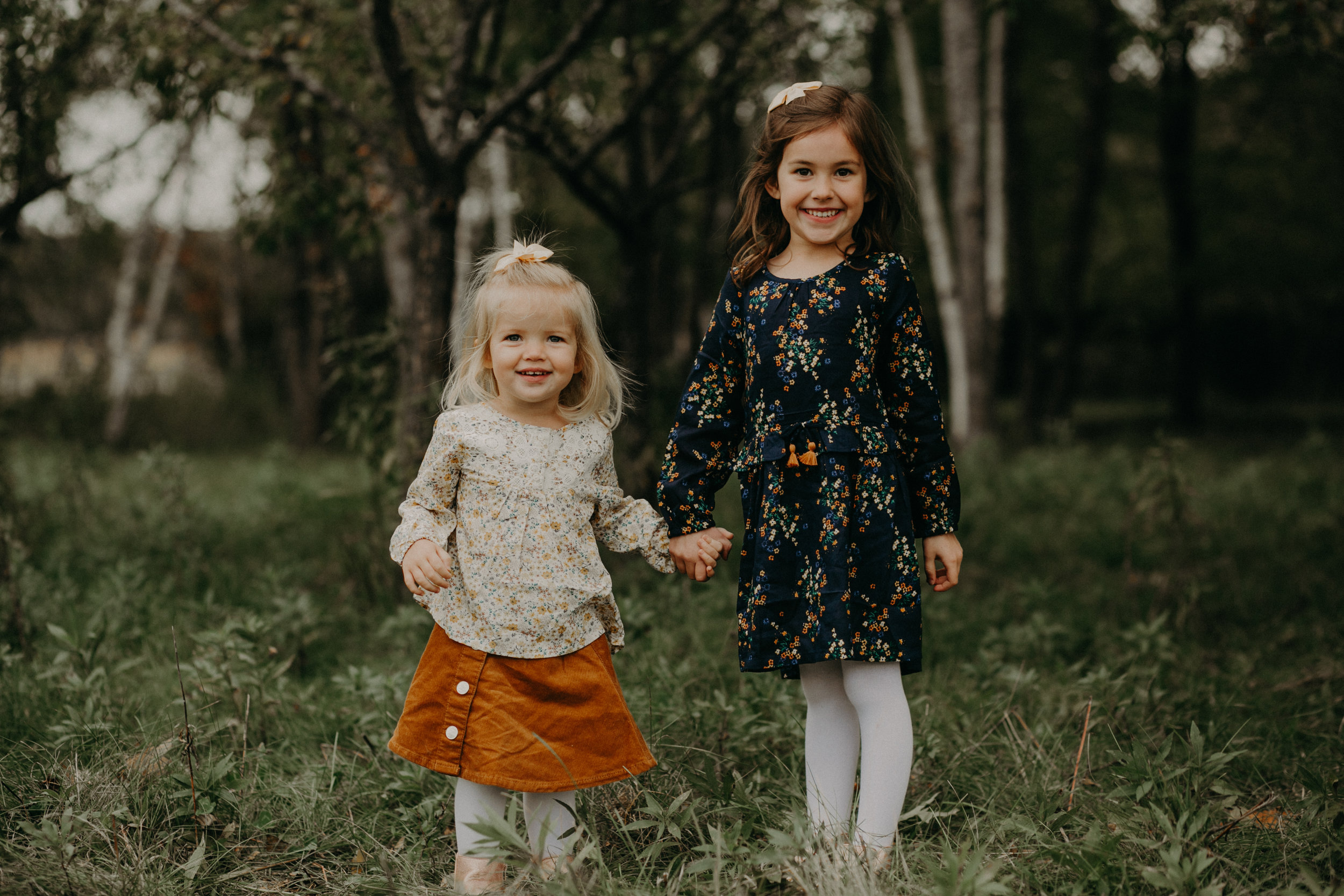 sisters from Woodbury MN hold hands during lifestyle family photo session