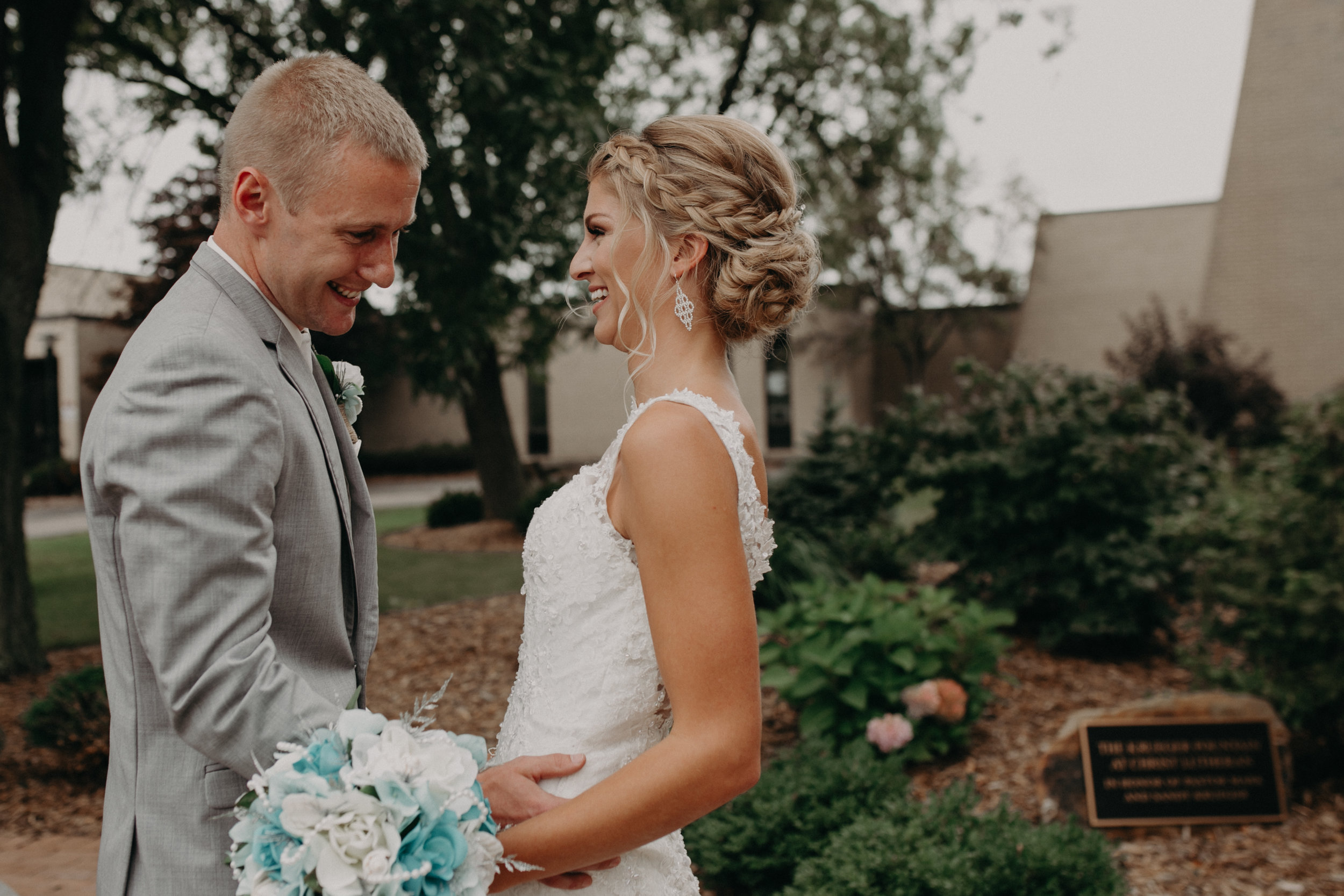 groom blushes as he sees his bride for the first time before his wedding at Christ Lutheran Church in Marshfield WI