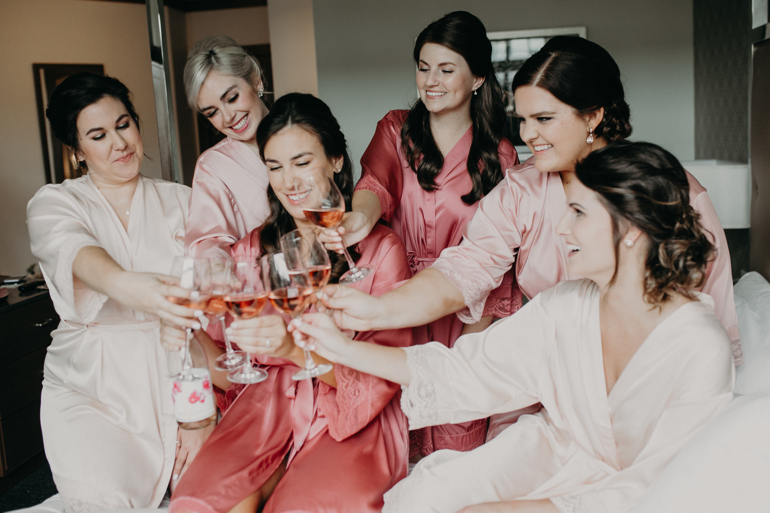 pink bride tribe getting ready for a lakeside wedding and drinking champagne in Wayzata MN at Hotel Landing