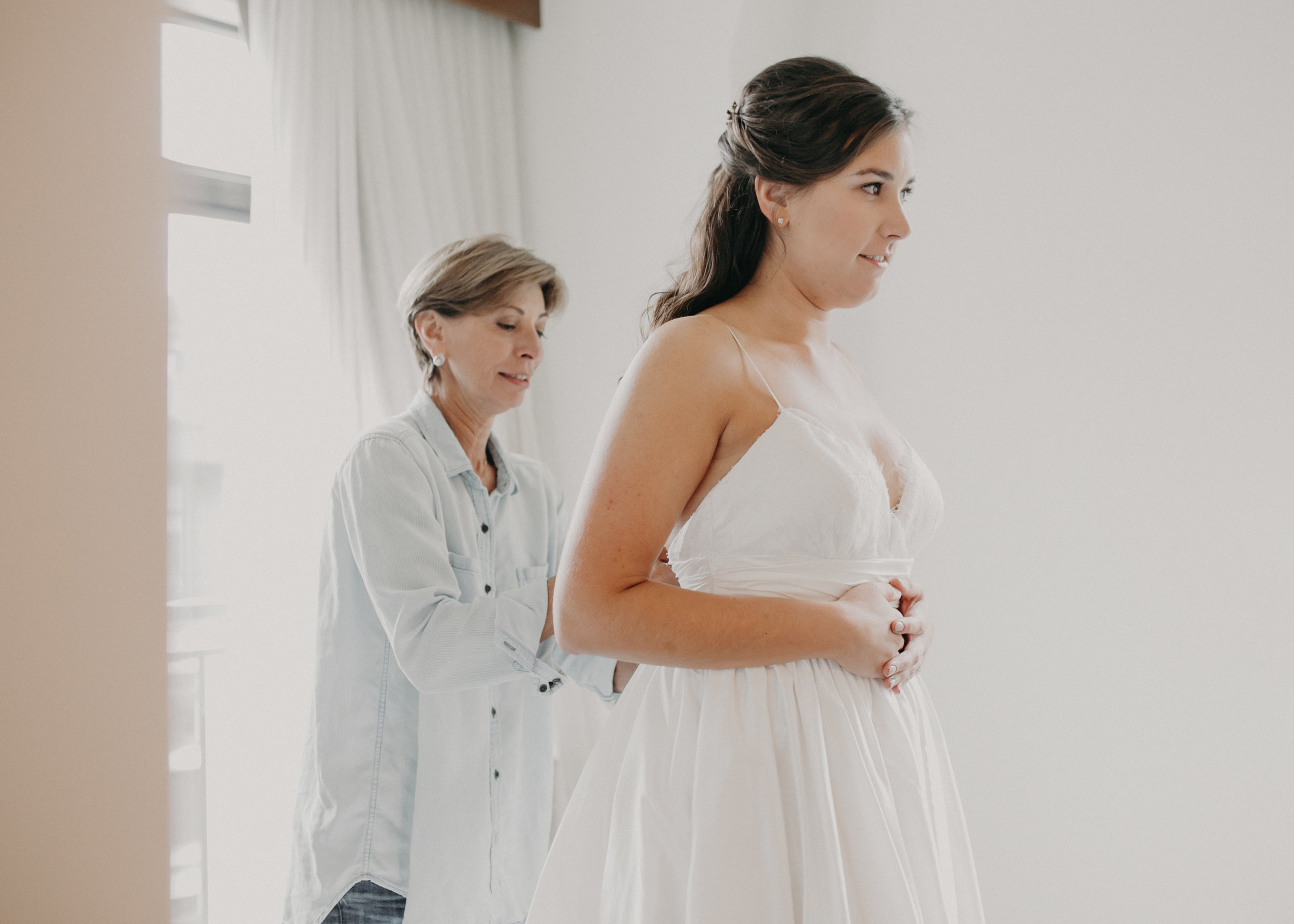 mother of the bride helps bride get into her wedding dress at Hotel Landing in Wayzata MN