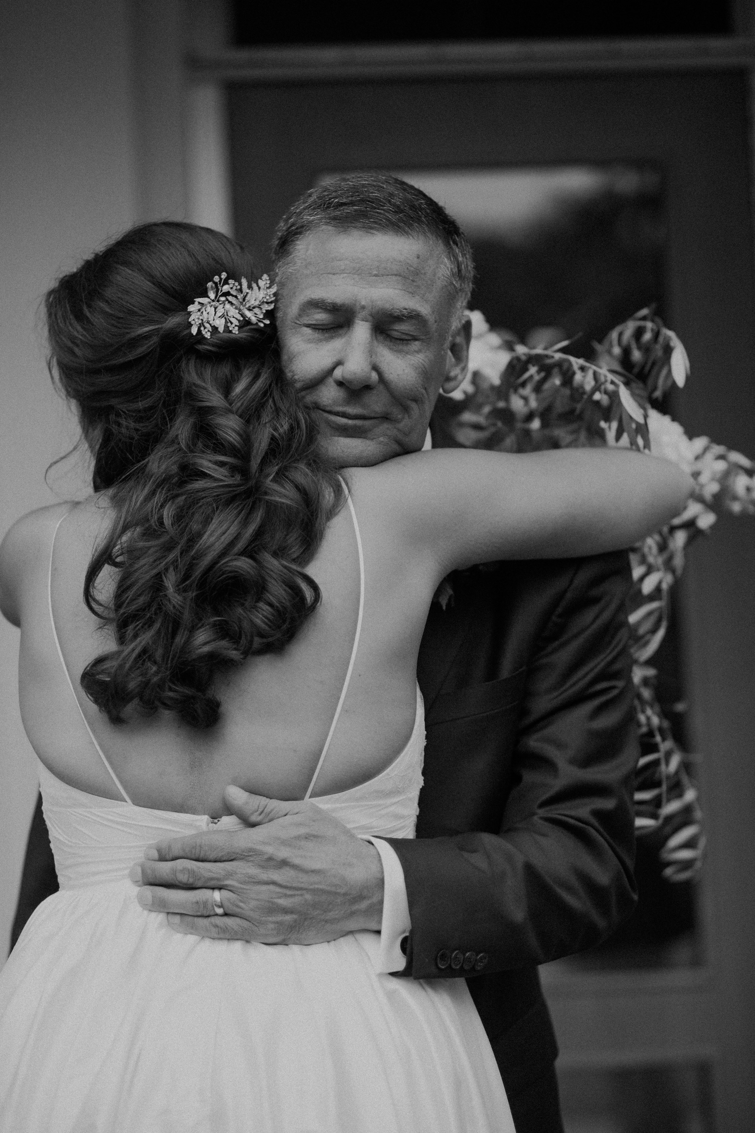 father of the bride and the bride hug during a first look moment at her lakeside wedding in Wayzata MN