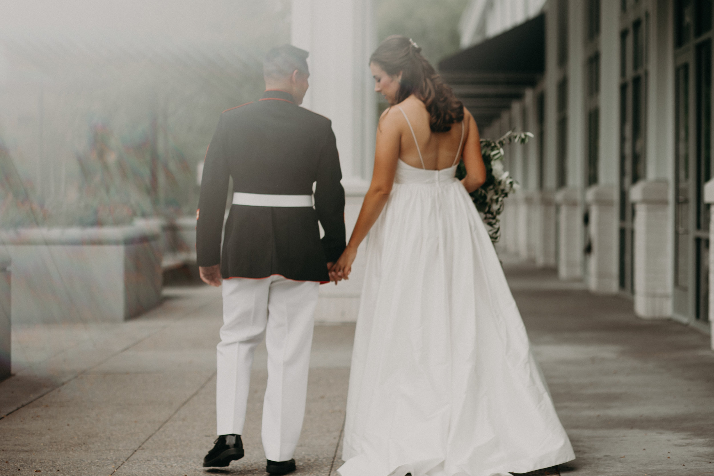 bride and military groom hold hands in front of Hotel Landing in Wayzata MN before their lake side wedding by Lake Minnetonka