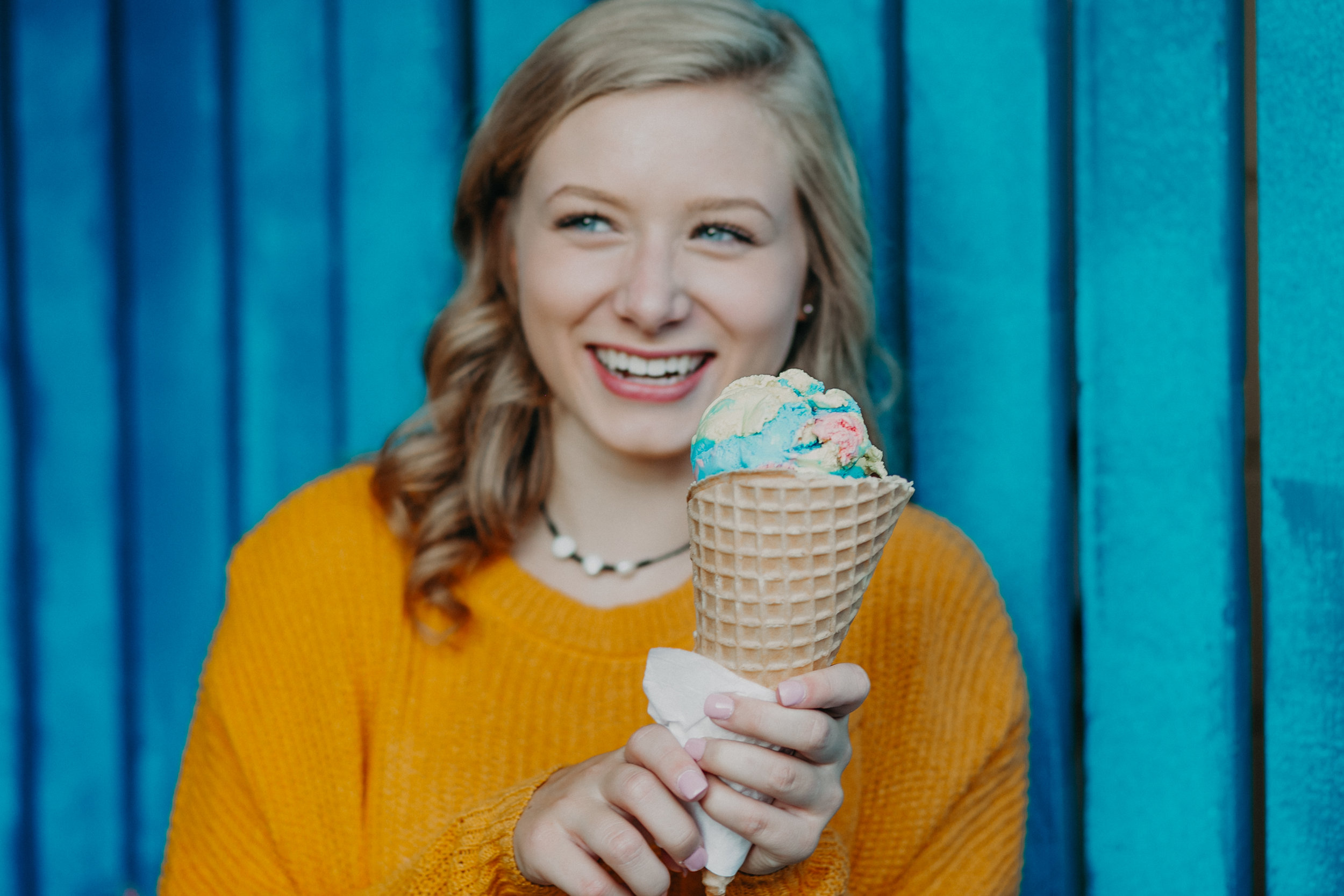 superman ice cream cone held by a smiling senior during her senior photo session in Hudson WI