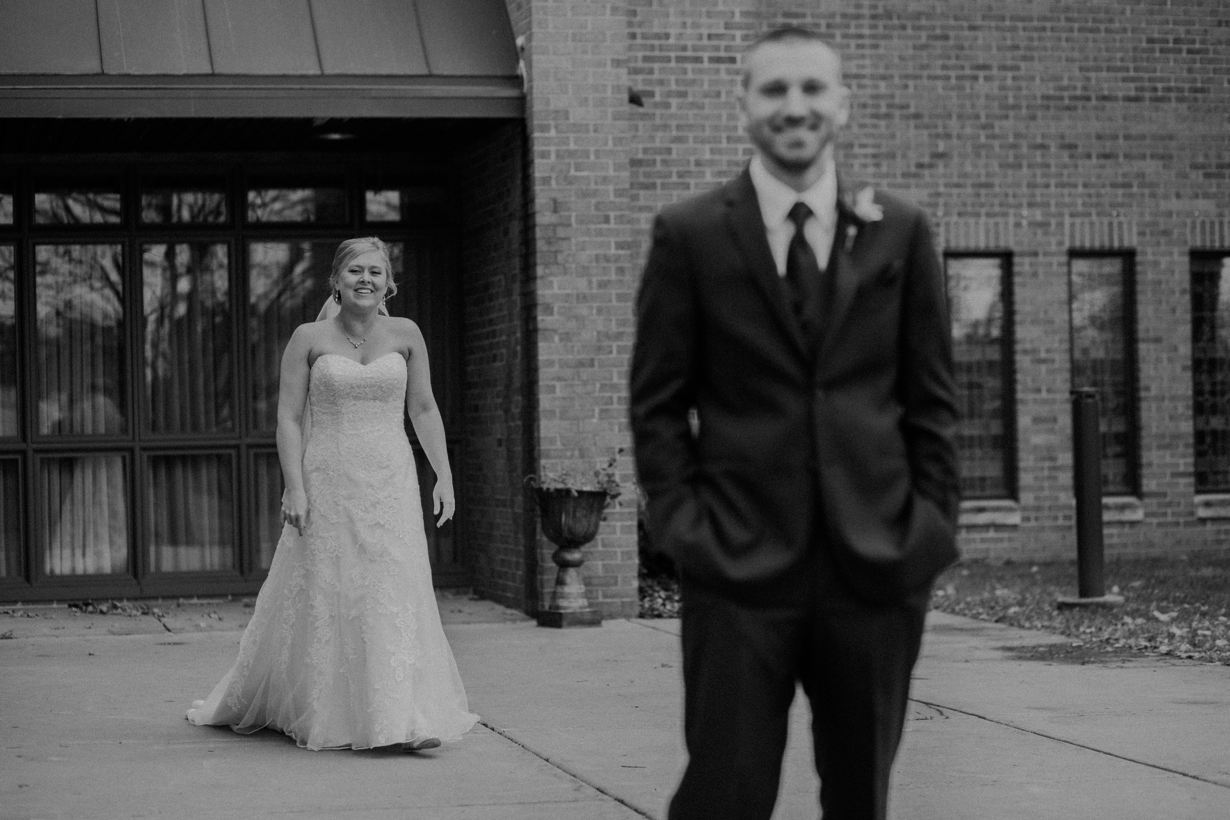 black and white photo of bride and groom's first look on wedding day at St Bridget's Catholic Church in River Falls