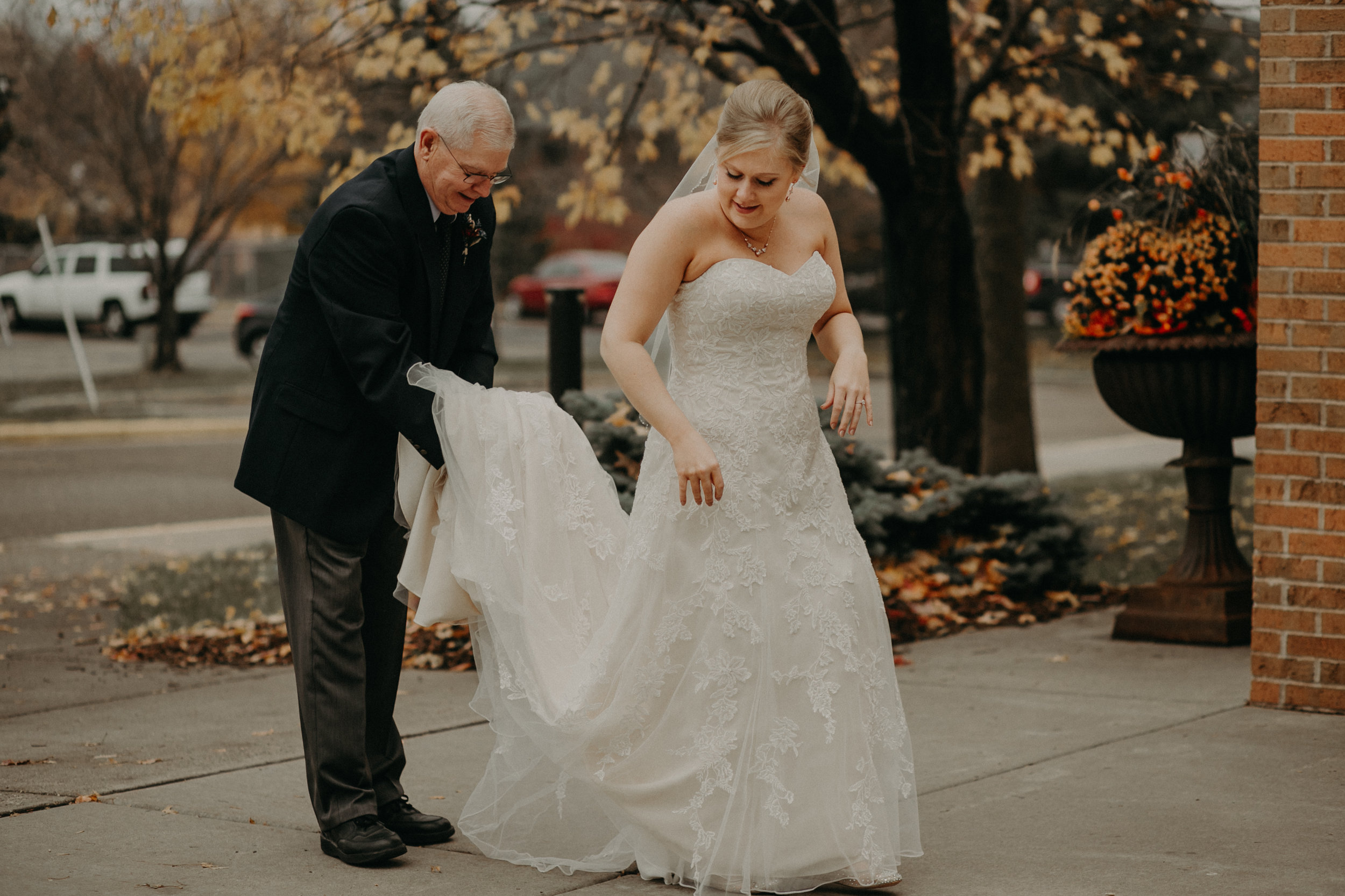 Grandfather holds bride's dress during first look at her wedding in River Falls