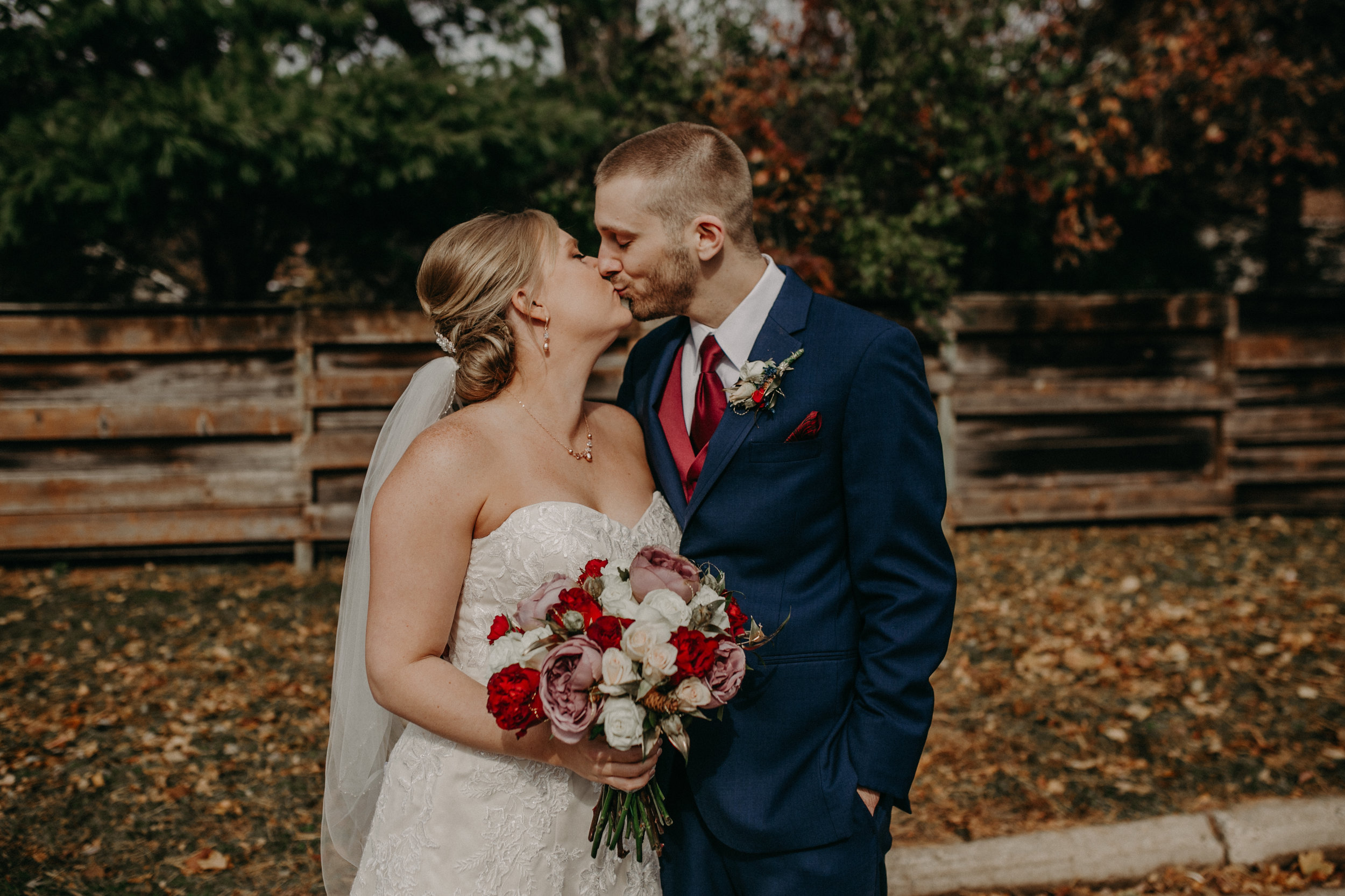 bride and groom kiss during their wedding in River Falls WI on a crisp October day in 2018