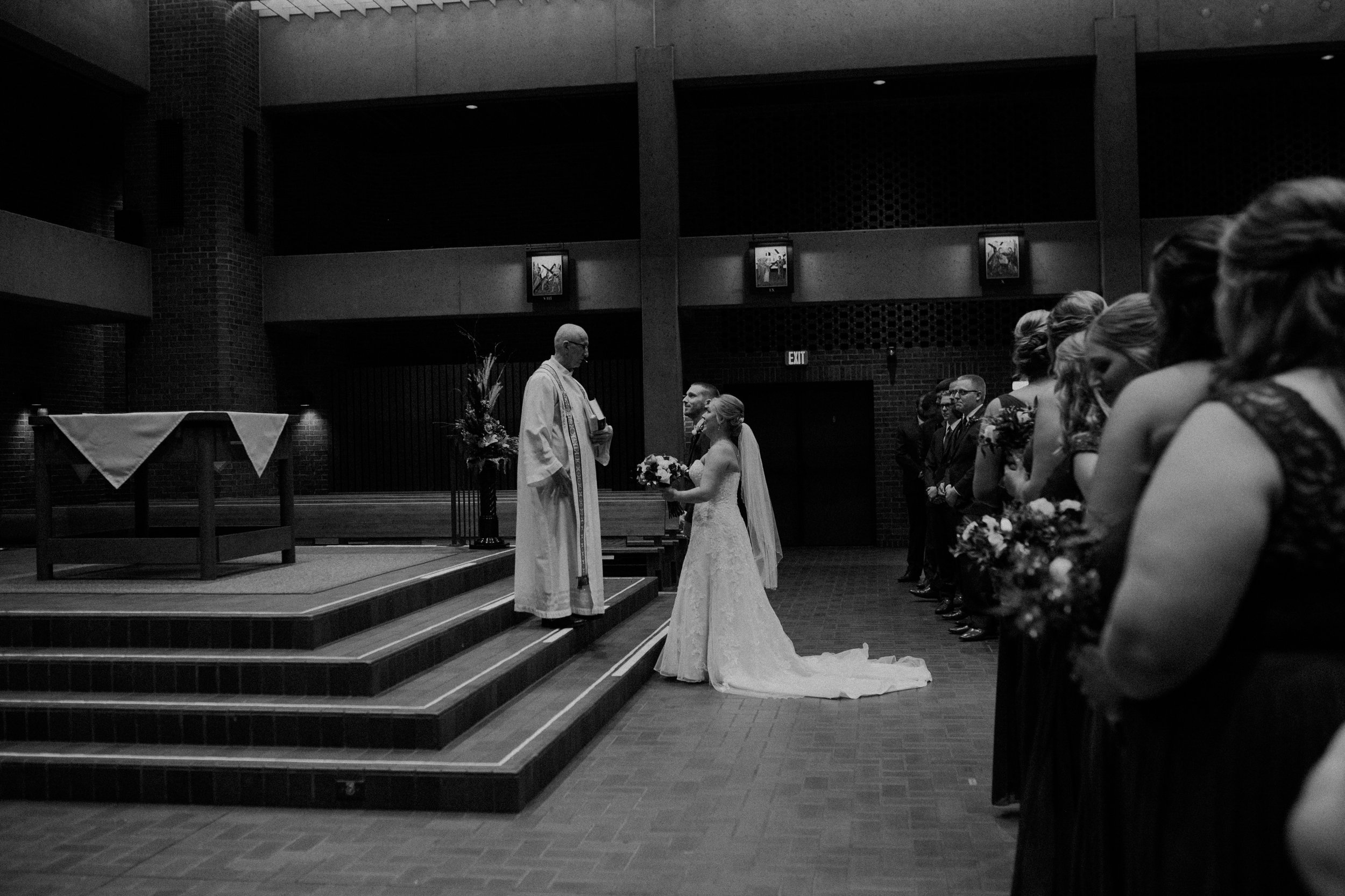 black and white photo of bride, groom, and Father at St Bridget's Catholic Church in River Falls WI during their ceremony