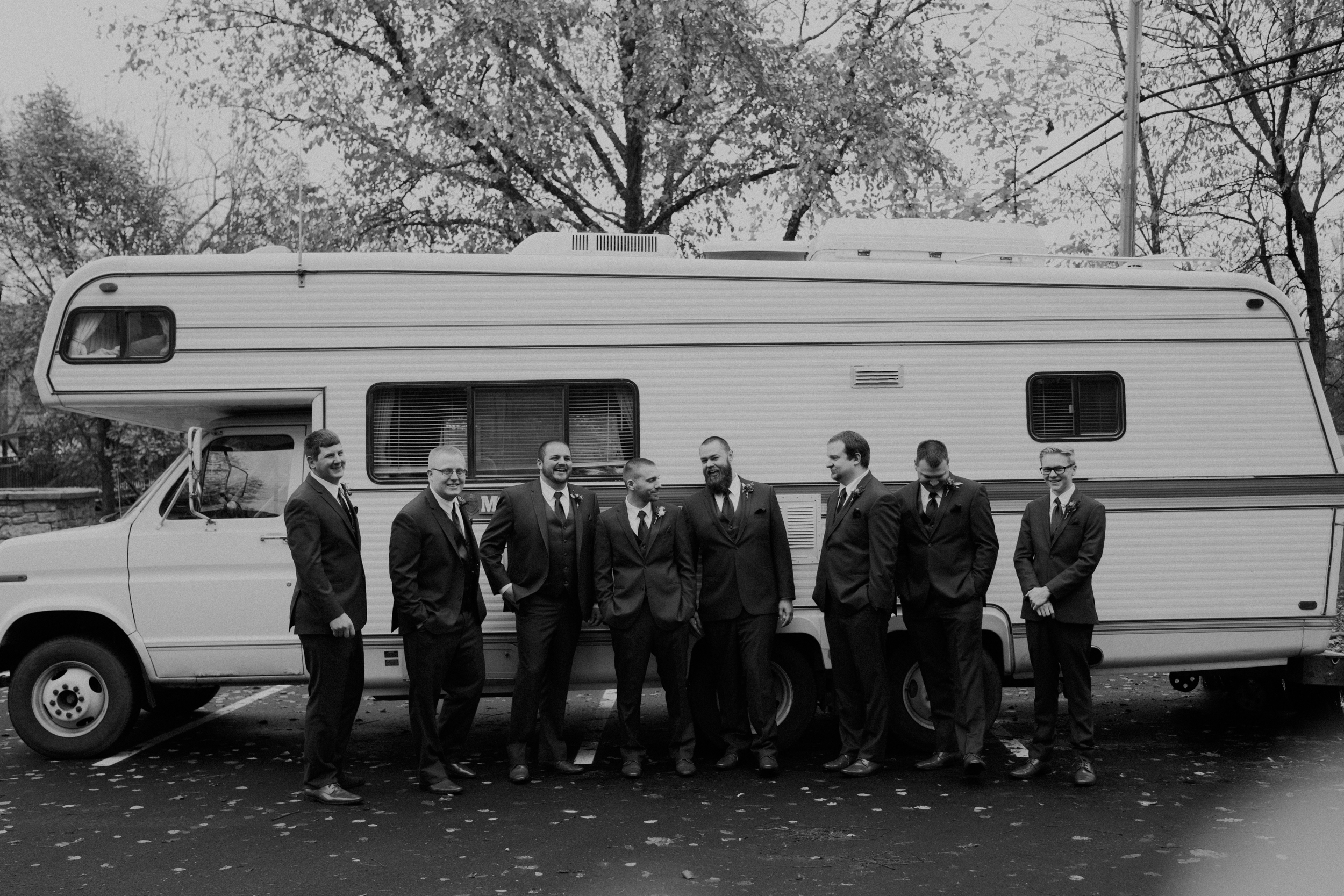 grooms and groomsmen pose in front of an RV at Heritage park in River Falls WI