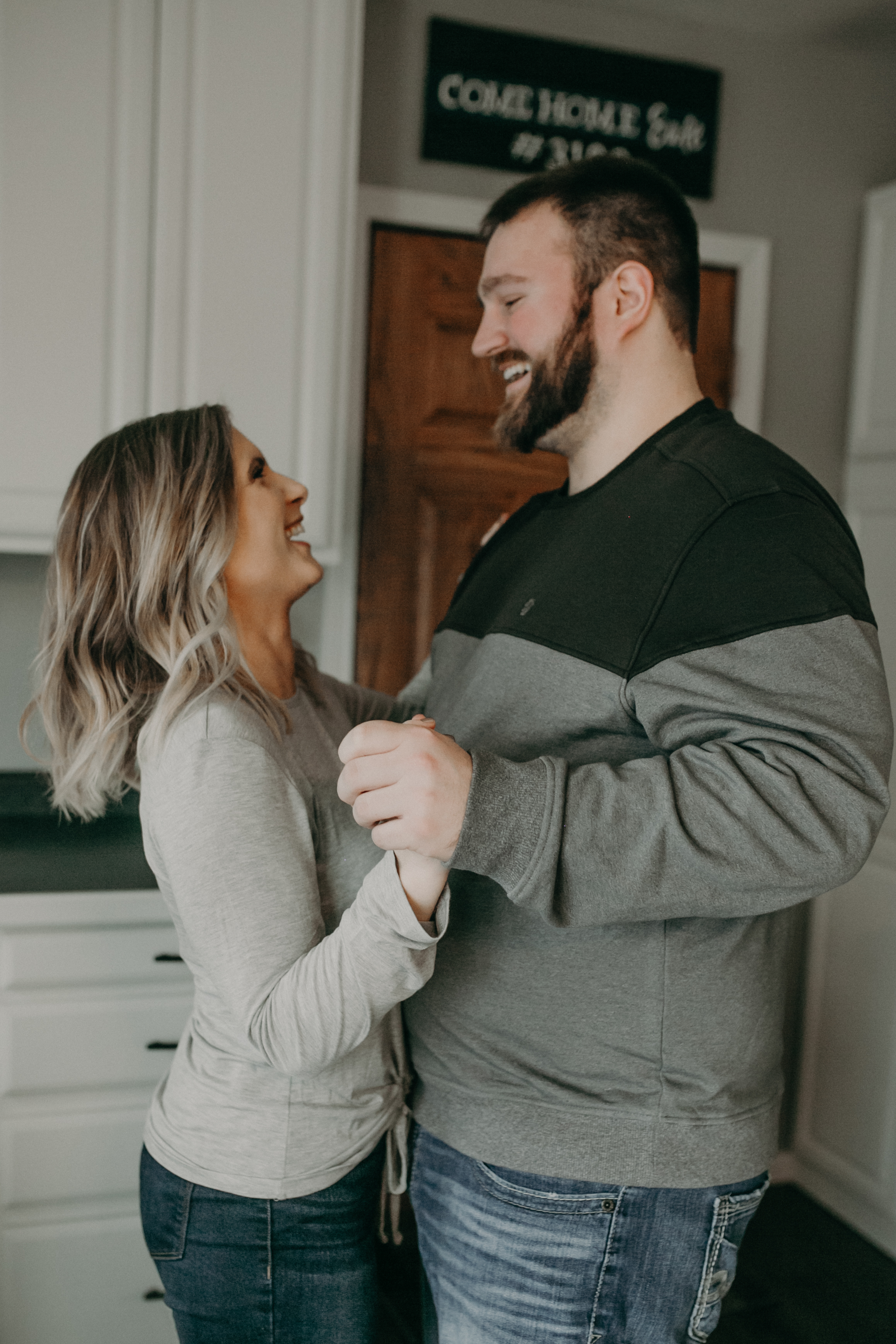 a couple dances in their kitchen during their in home engagement session in Wisconsin