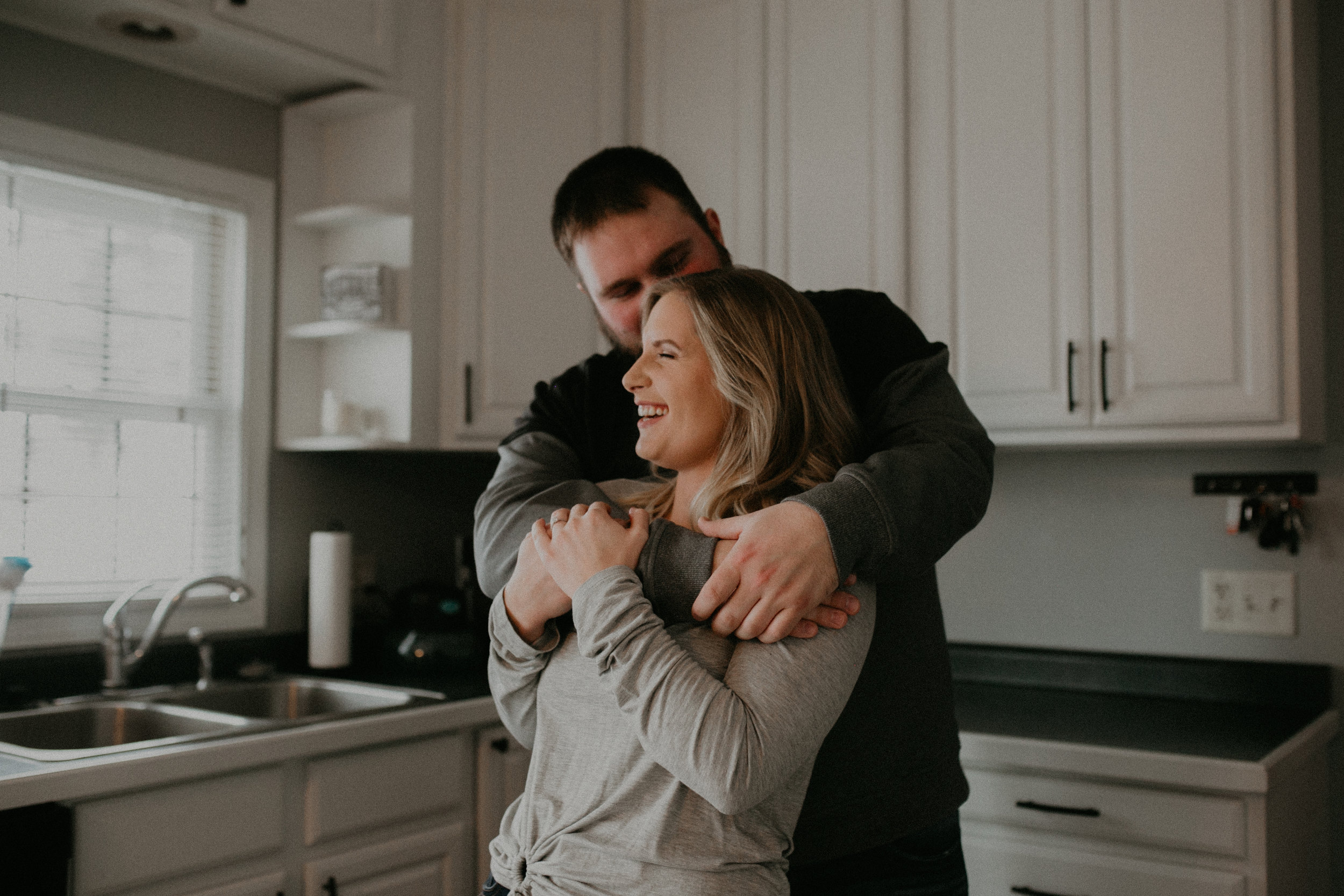 a couple dances and laughs in their kitchen during their engagement session in Athens WI