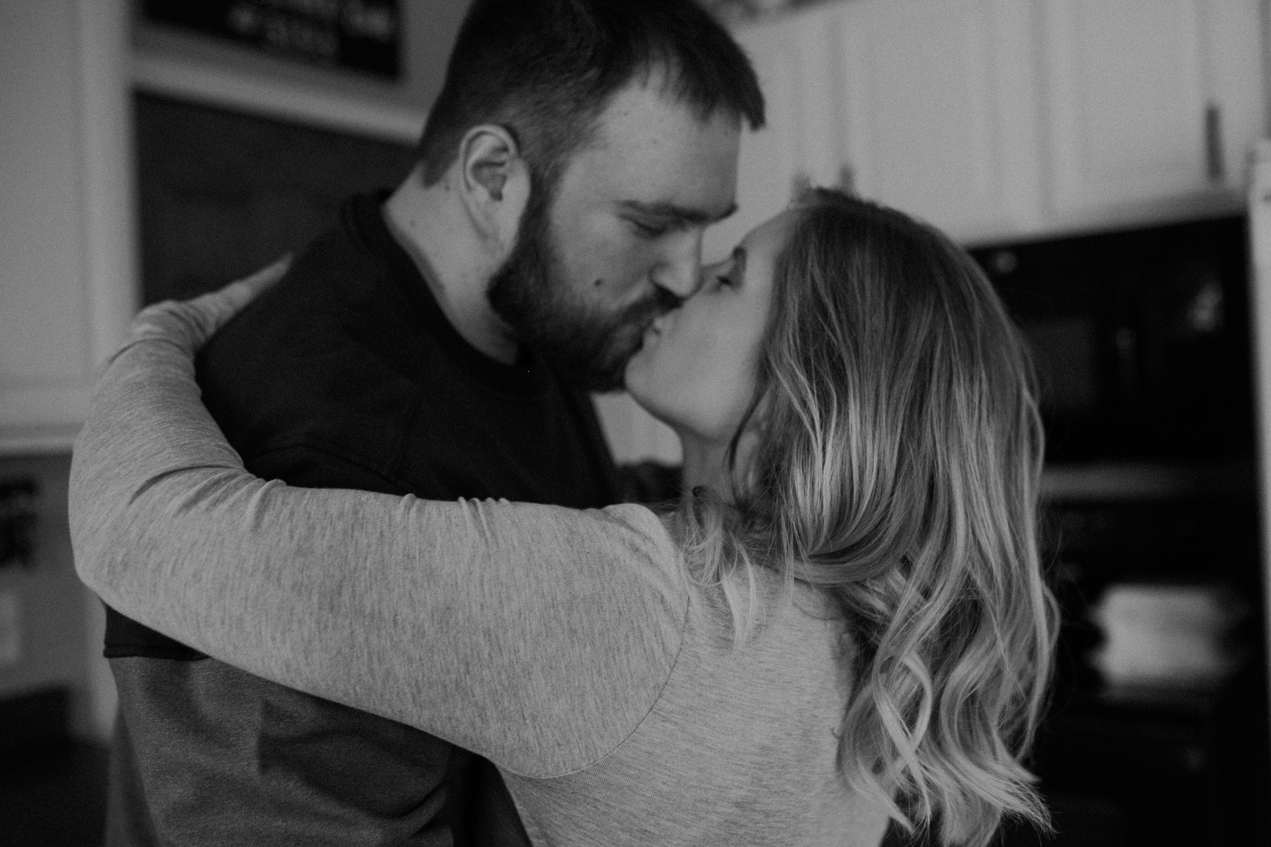 black and white photo of an engaged couple in their home kissing in the kitchen