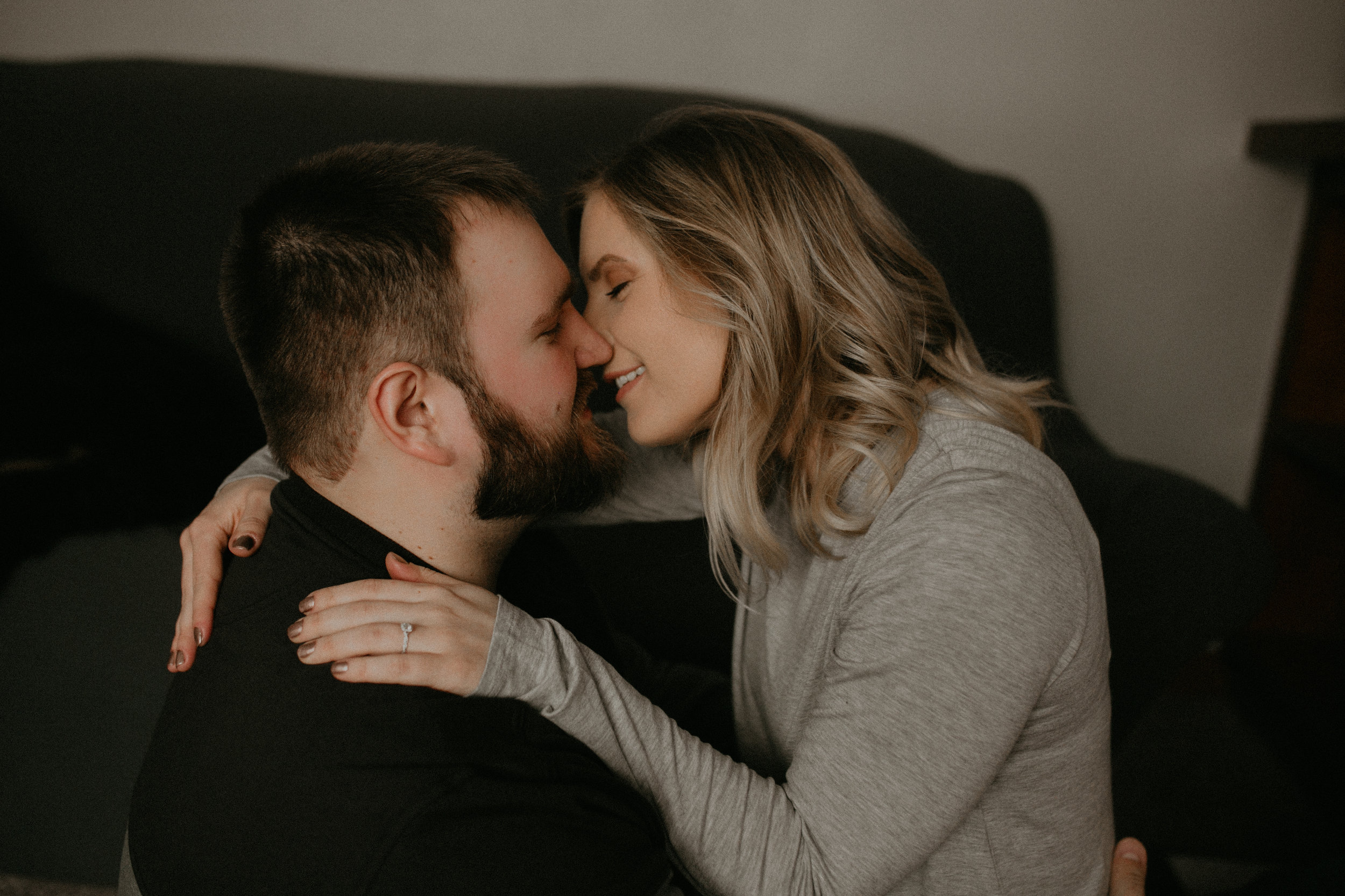Athens WI couple kisses in their living room during their engagement session