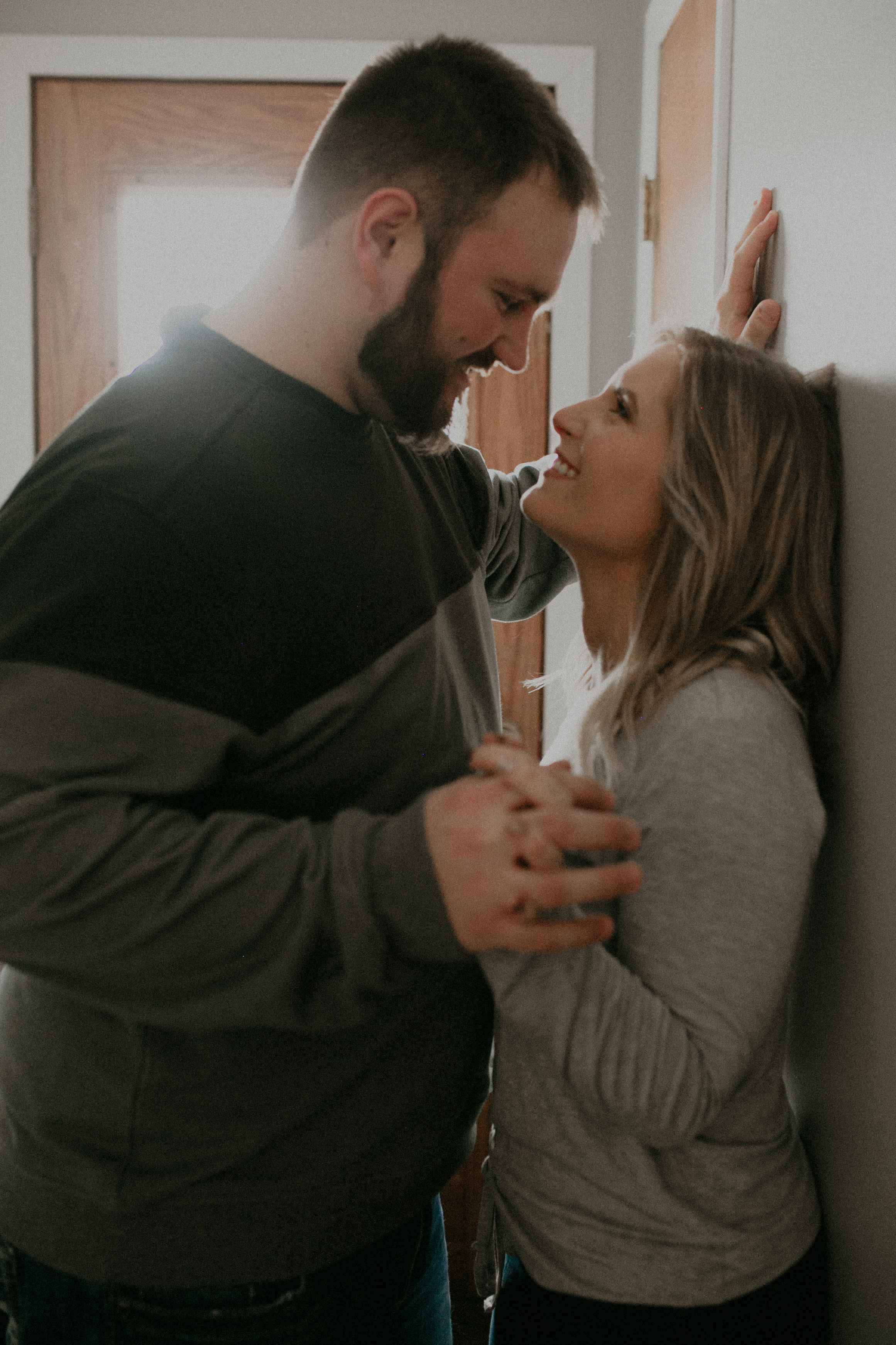 fiance lovingly stares at her soon-to-be husband during engagement photos in their home