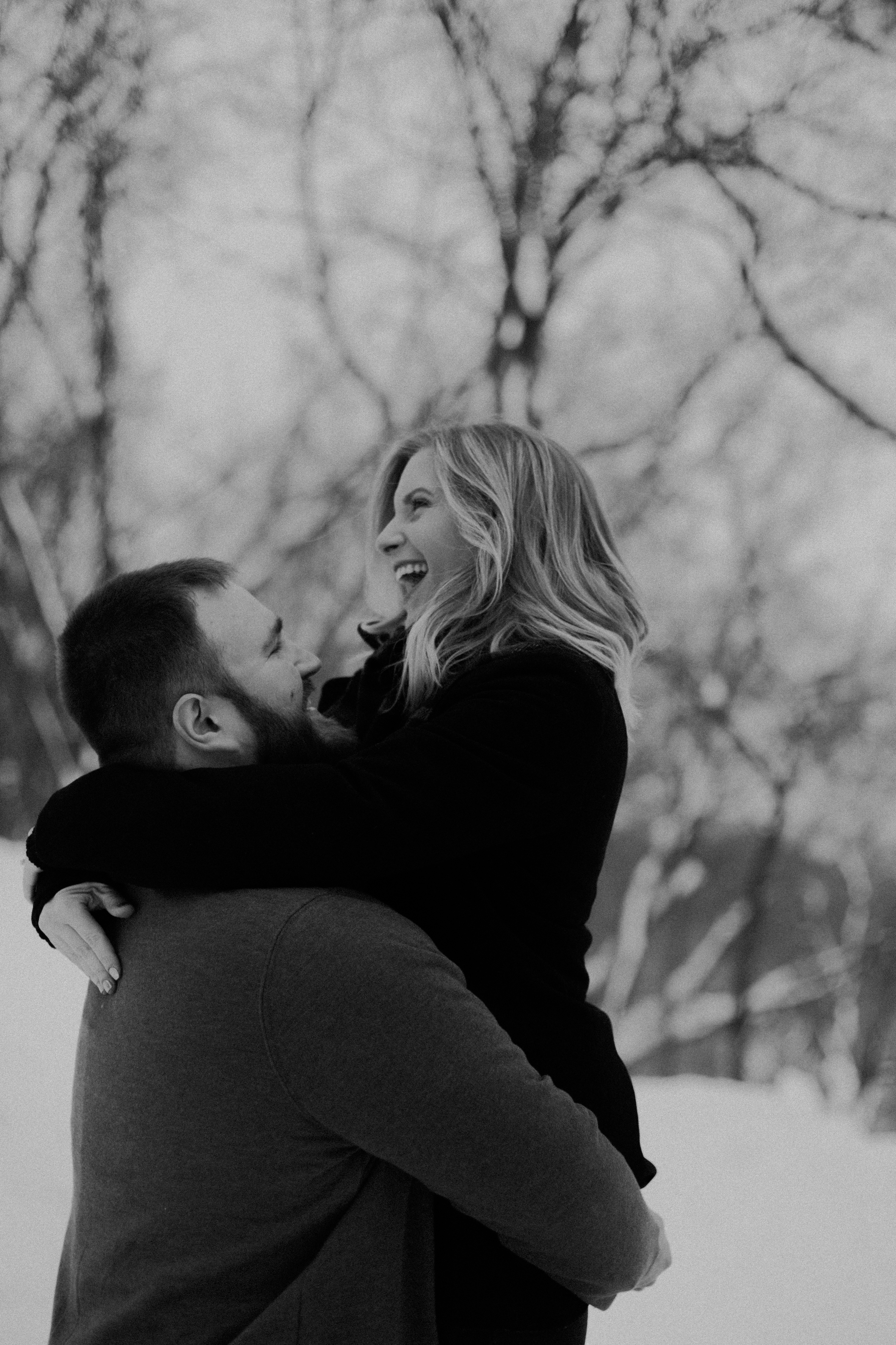 happy engaged couple flirts in the snow during their lifestyle engagement session in Athens WI