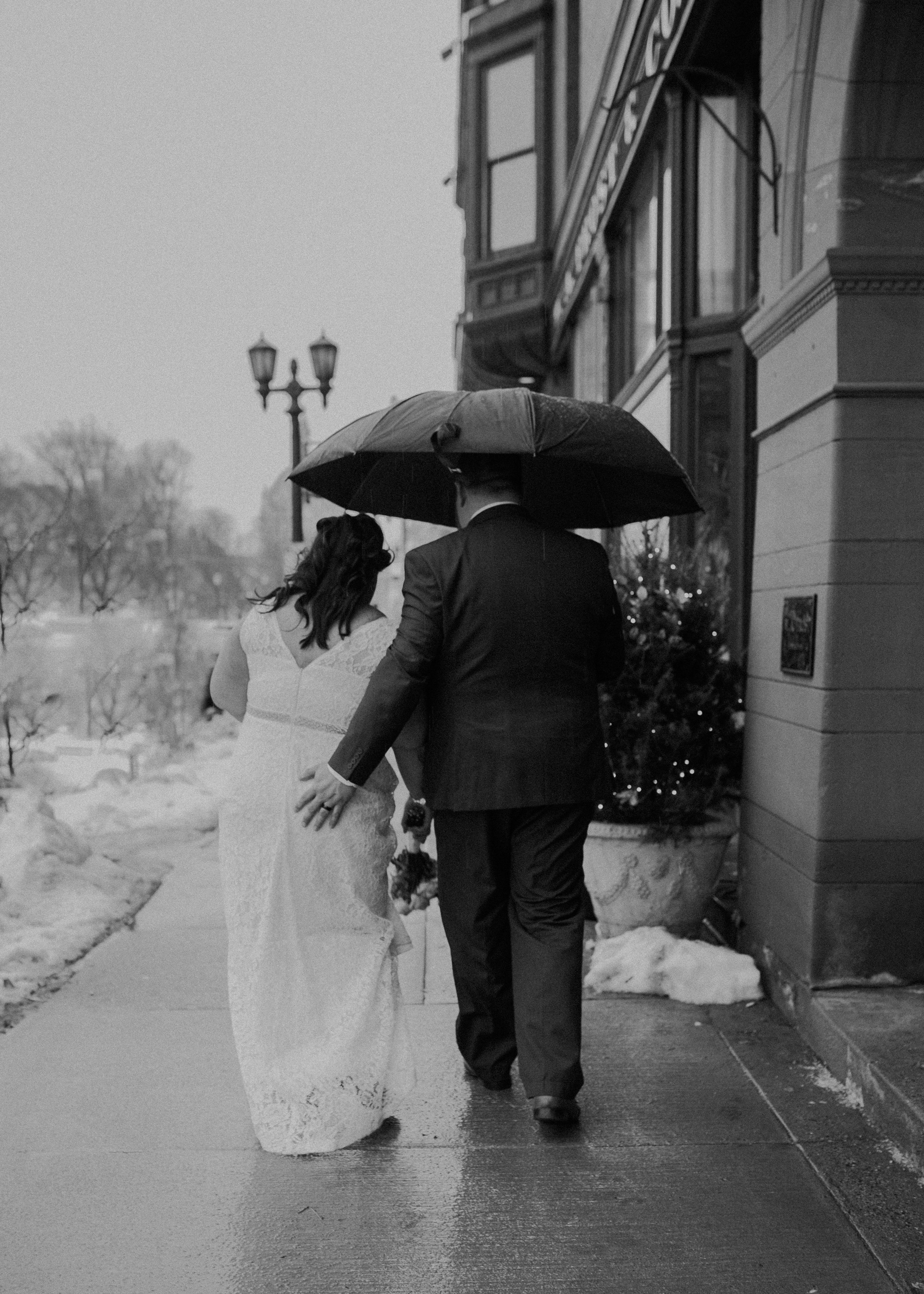 A black and white photo of a couple strolling along the streets of St Paul holding an umbrella after their March 2019 wedding on Historic Cathedral Hill