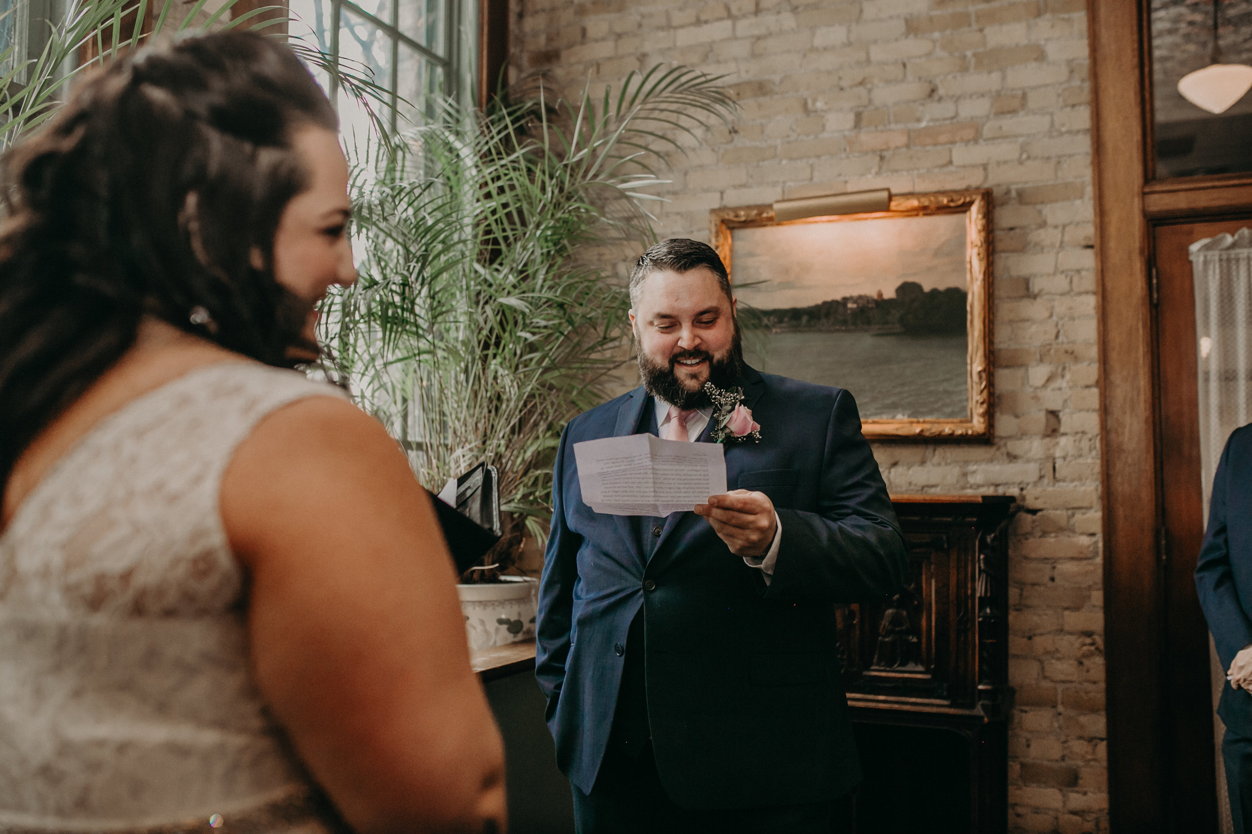 A Twin Cities groom reads his vows to his wife during their intimate ceremony at W. A. Frost in St Paul MN