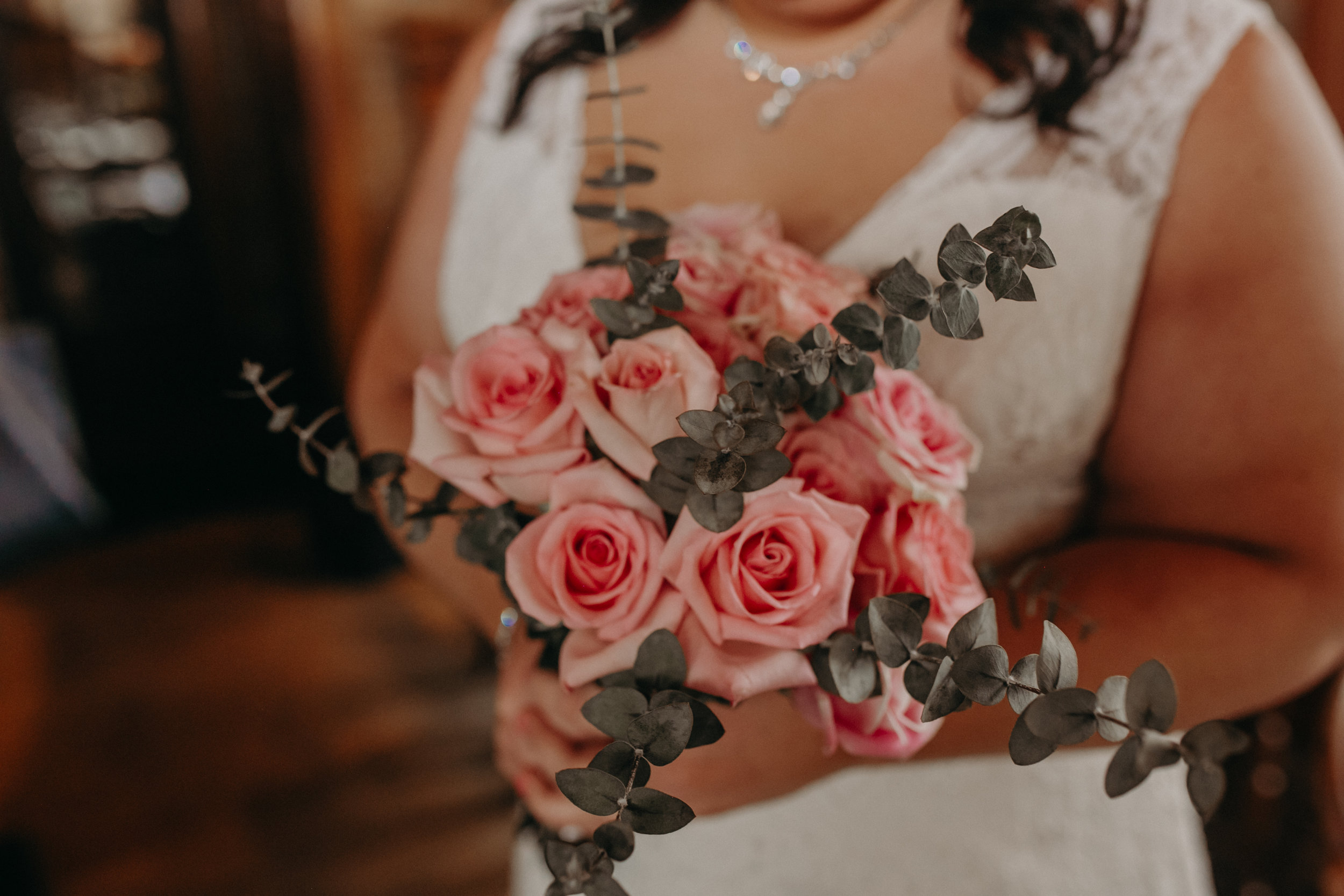 A bride at W.A. Frost holds her wedding bouquet made from pink roses and eucalyptus