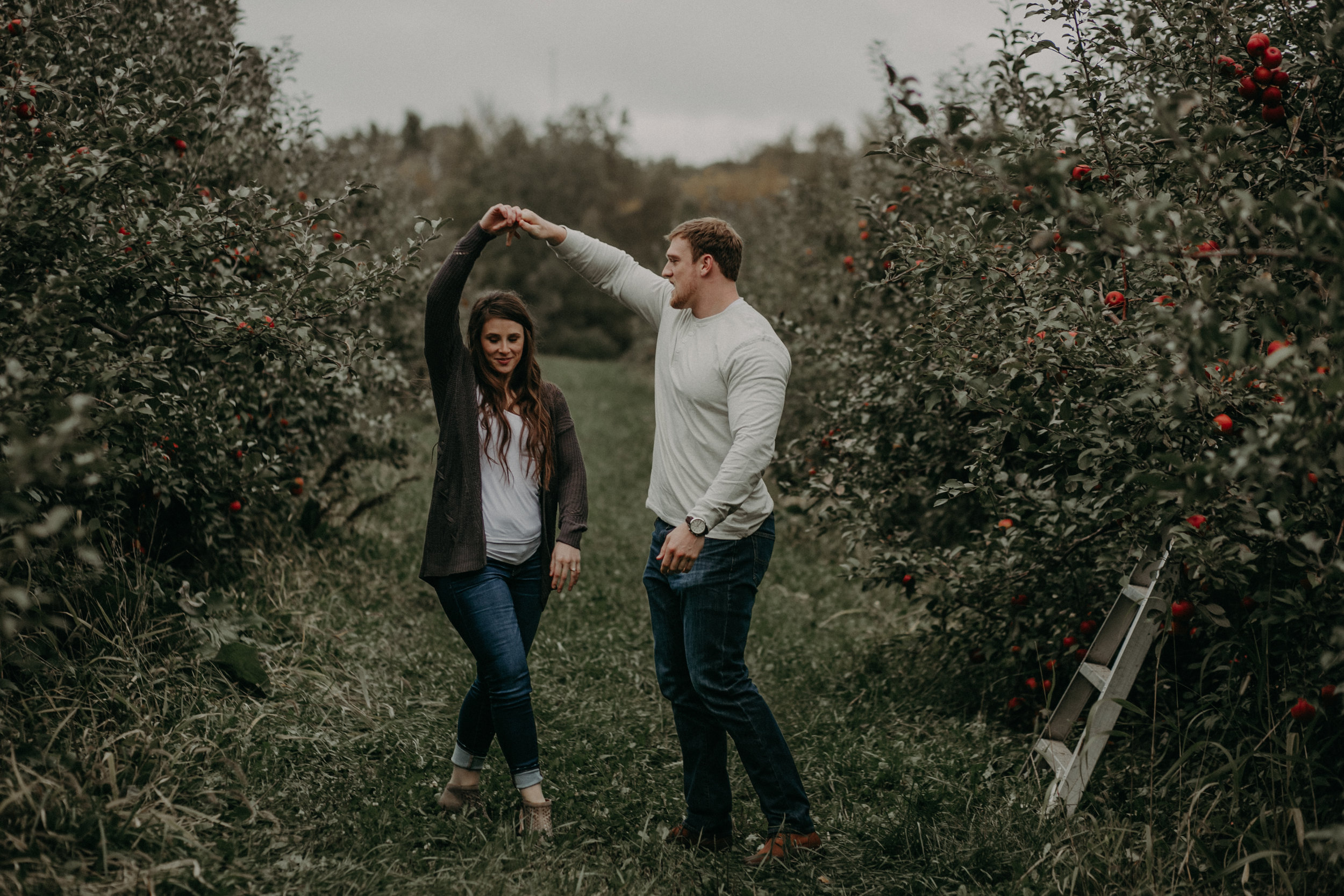 A couple dances amongst the apple tree orchard in Hastings MN during their engagement session