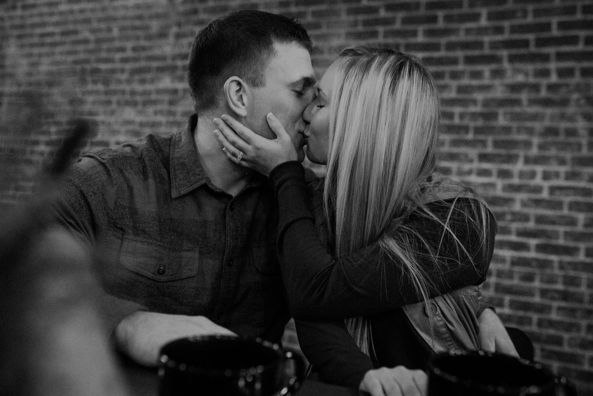 a couple kisses during their engagement session at Revolution Coffee in Black River Falls WI