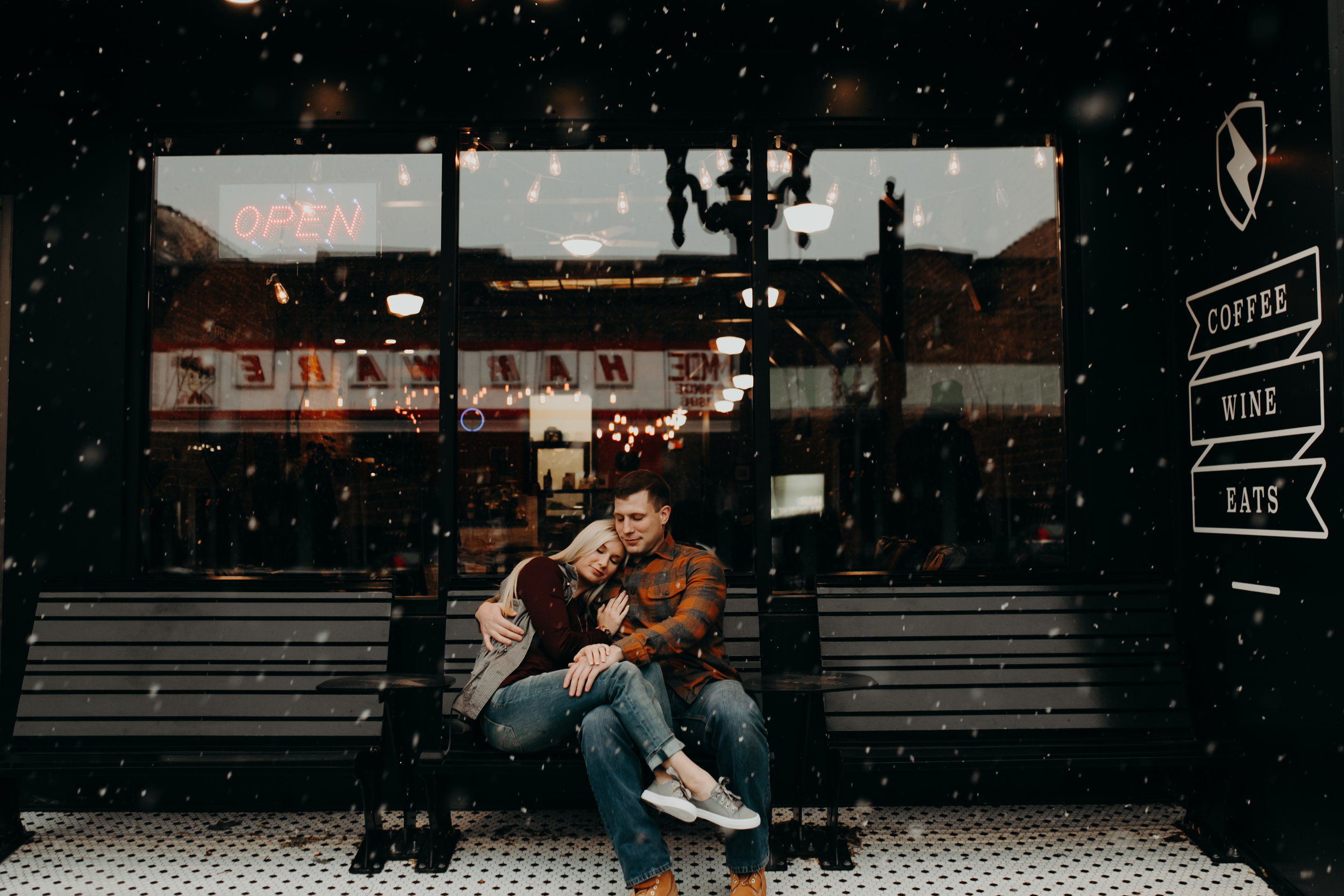 a couple snuggles outside while it snows in front of Revolution Coffee in downtown Black River Falls