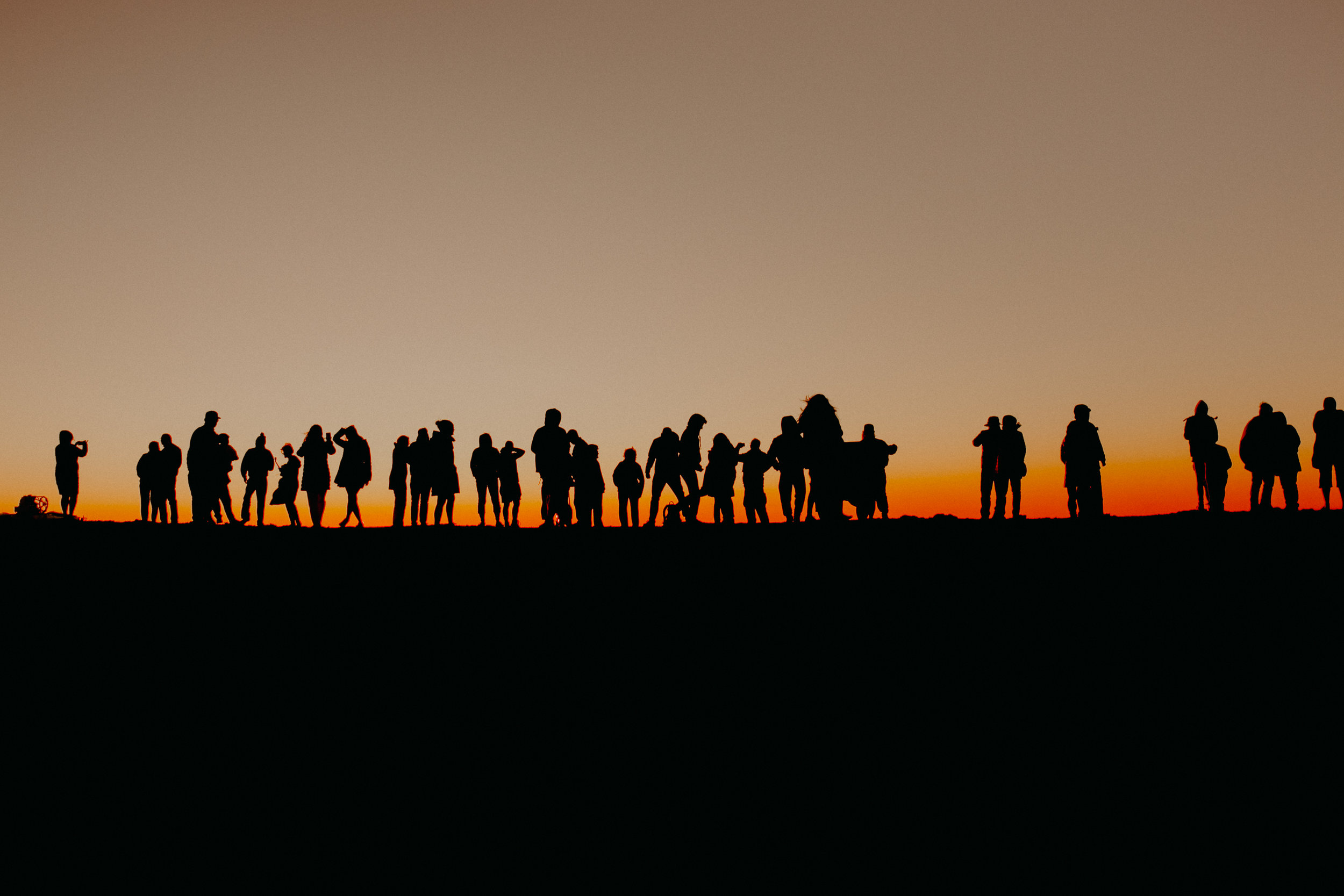 a row of people taking photos of the sun set from Haleakala Volcano in Maui Hawaii